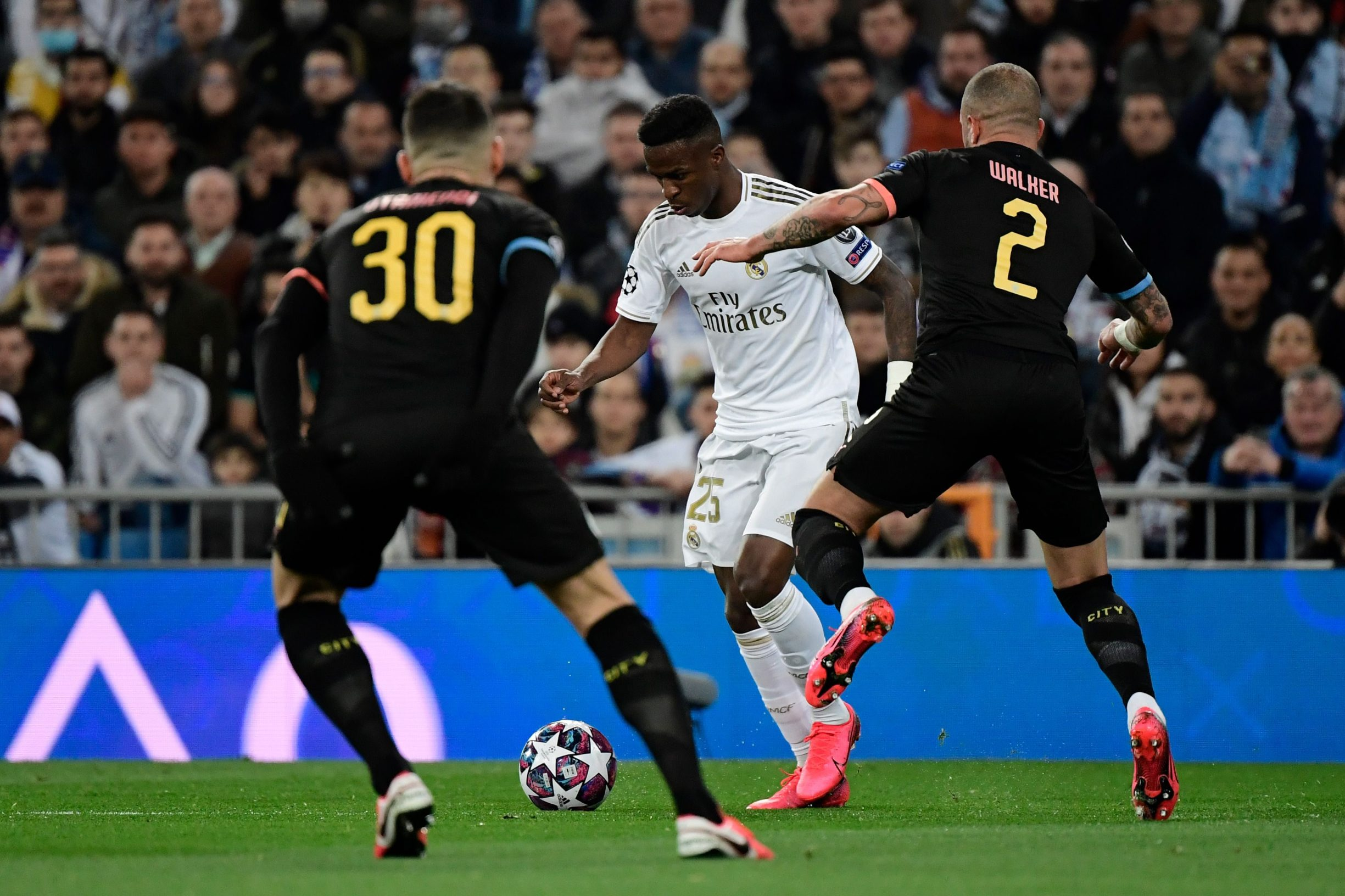 Real Madrid's Brazilian forward Vinicius Junior (C) vies with Manchester City's English defender Kyle Walker during the UEFA Champions League round of 16 first-leg football match between Real Madrid CF and Manchester City at the Santiago Bernabeu stadium in Madrid on February 26, 2020. (Photo by JAVIER SORIANO / AFP)