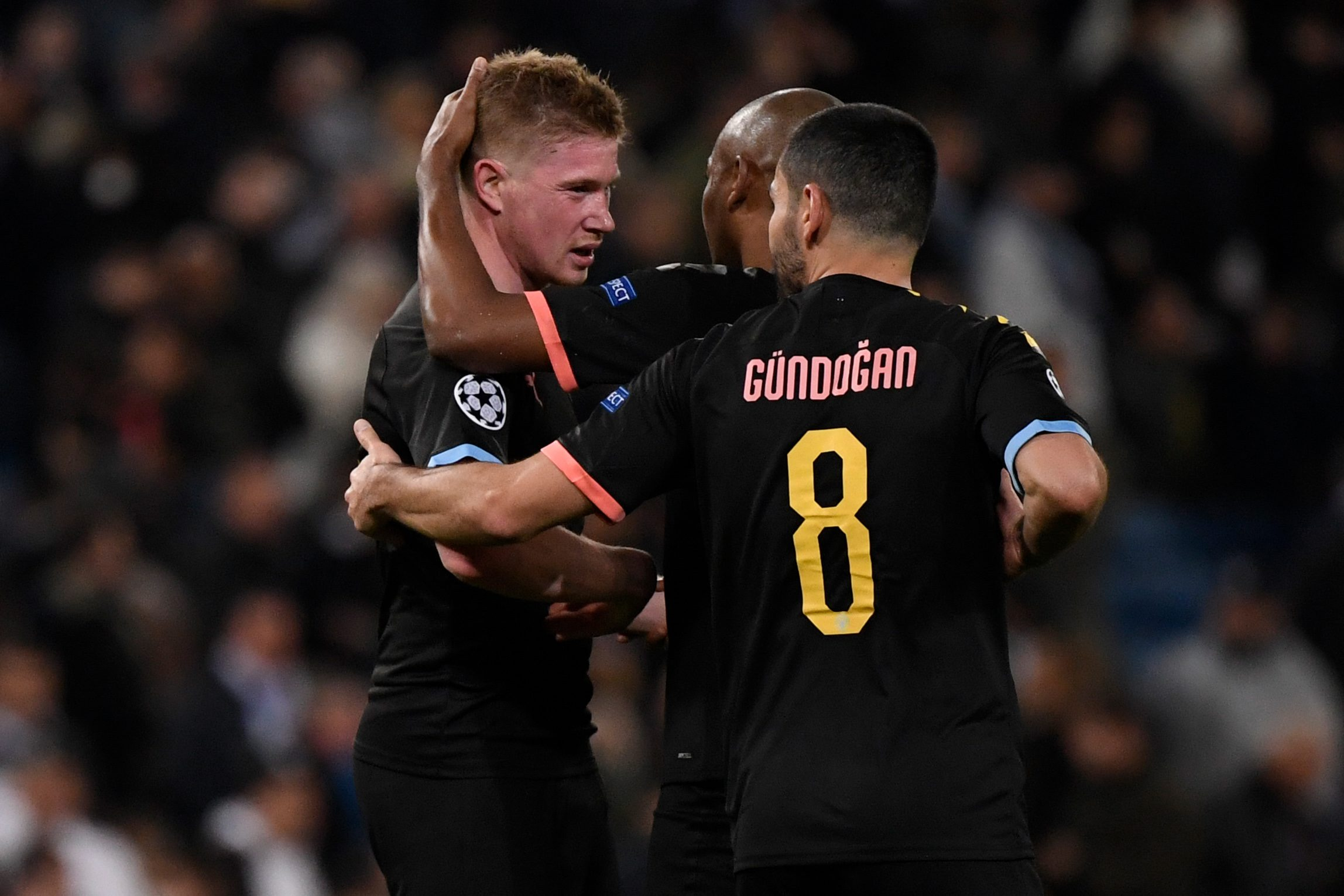 Manchester City's Belgian midfielder Kevin De Bruyne (L) and teammates celebrate their win at the end of the UEFA Champions League round of 16 first-leg football match between Real Madrid CF and Manchester City at the Santiago Bernabeu stadium in Madrid on February 26, 2020. (Photo by PIERRE-PHILIPPE MARCOU / AFP)