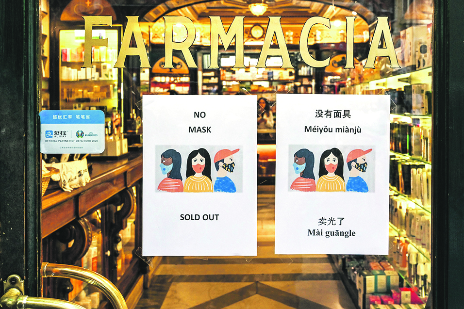 A sign advising clients in various languages, including Chinese, that respiratory masks are sold out, is displayed on January 29, 2020 at a pharmacy in downtown Rome, in the wake of the 2019-nCoV coronavirus, a virus similar to the SARS pathogen, spreading around the world since emerging in a market in the central Chinese city of Wuhan. - The Italian government said on January 29, 2020 it was sending a plane to evacuate citizens from the Chinese city of Wuhan, the epicentre of a deadly SARS-like virus, as WHO chief called new emergency talks on the virus situation. (Photo by Alberto PIZZOLI / AFP)