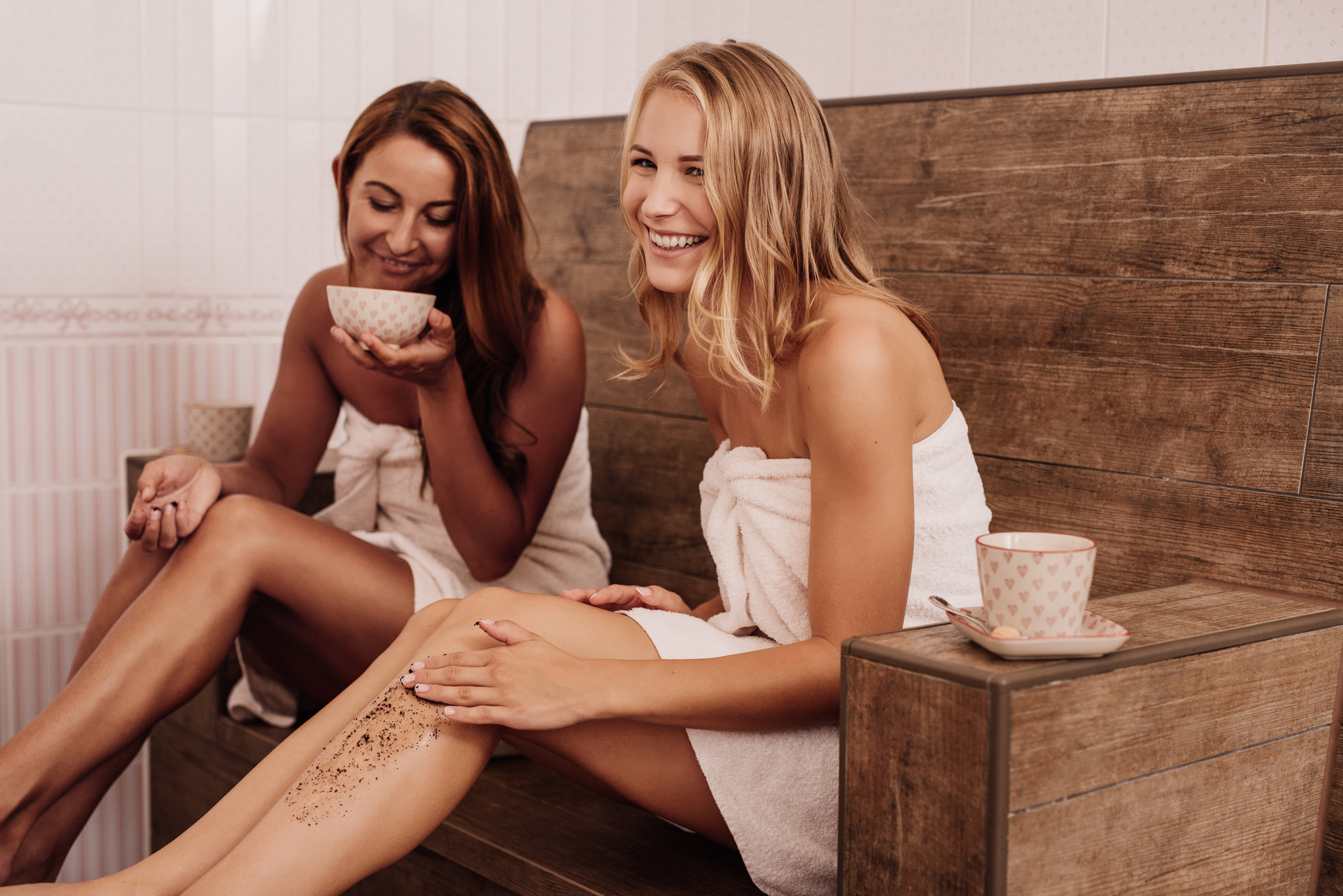 Women crubbing with coffee in health spa Photo taken indoors of young women with beauty treatment