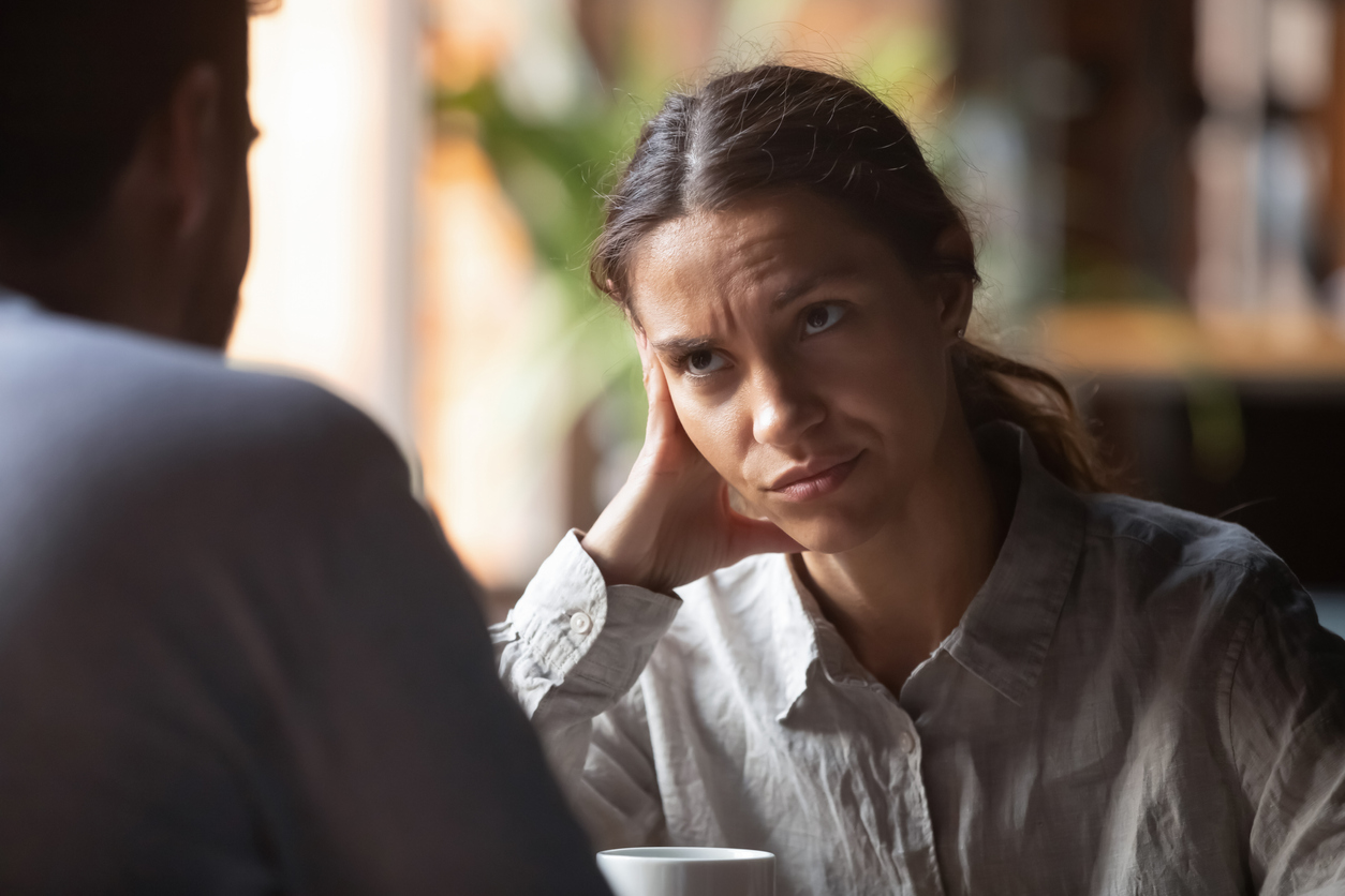 Focus on mixed race irritated young female sitting in cafeteria on speed dating with boring male rear view. Unsuccessful unlucky romantic date failure, bad first impression and poor companion concept