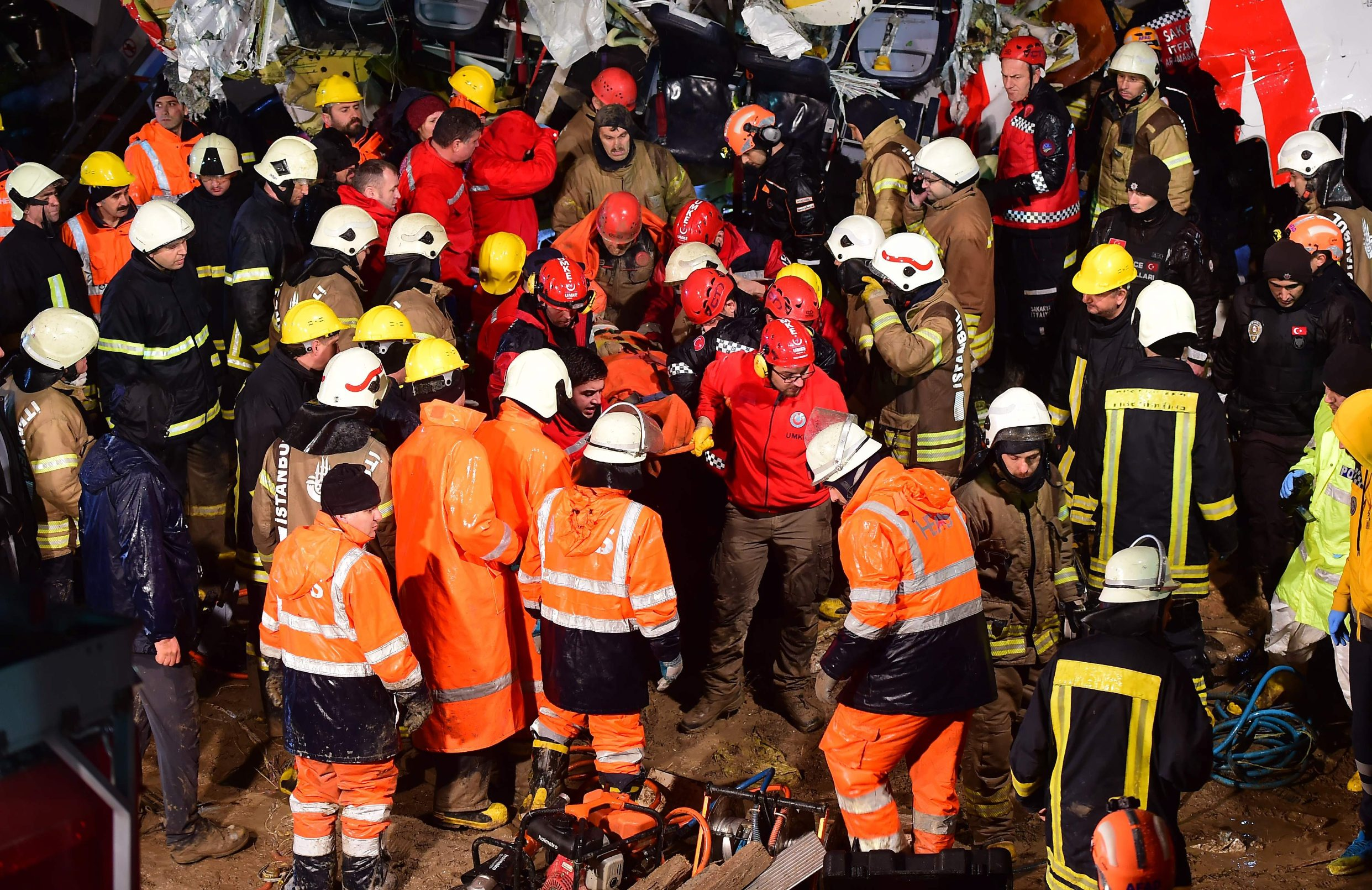 Rescuers carry a person extracted from the crash of a Pegasus Airlines Boeing 737 airplane, after it skidded off the runway upon landing at Sabiha Gokcen airport in Istanbul on February 5, 2020. - The plane carrying 171 passengers from the Aegean port city of Izmir split into three after landing in rough weather. Officials said no-one had lost their lives in the accident, but dozens of people were injured. (Photo by Yasin AKGUL / AFP)
