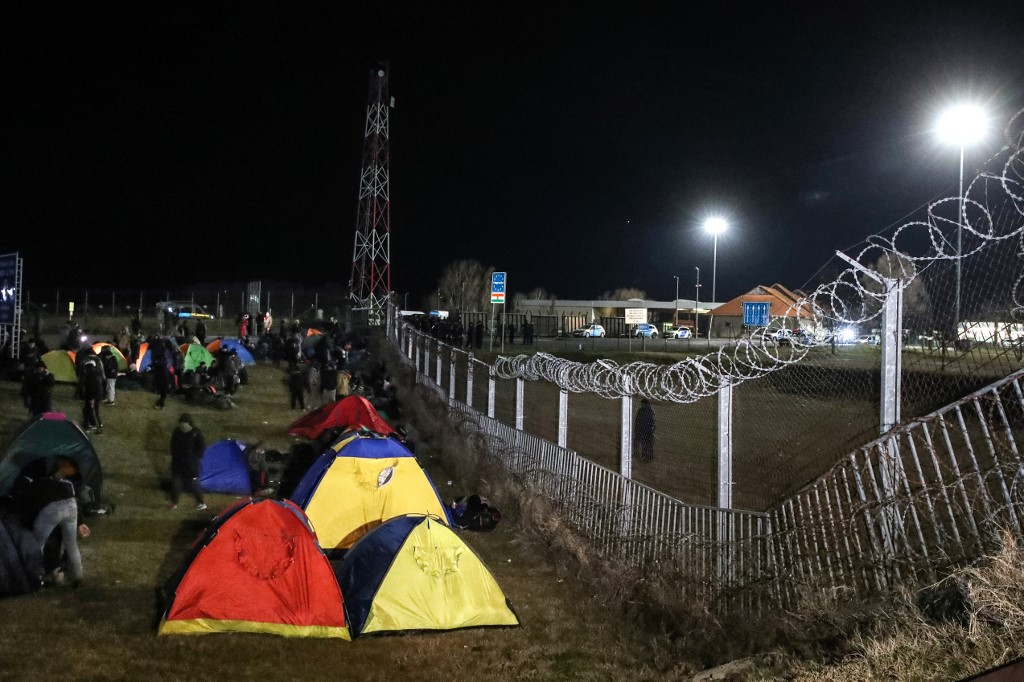 Migrants camp in tents next to the border fence at the Serbian Kelebija border village near Subotica on February 6, 2020, as the Tompa road border-crossing on the Hungarian side has been temporarily closed by the Hungarian police. - Hungarian police temporarily closed a Serbian border crossing on February 6 after a large migrant group showed up there and demanded to be let in. The attempt came a week after 60-70 people tried to get into Hungary at another Serbian border crossing under cover of night, prompting security staff to fire warning shots in the air. Hungarian police report a sharp rise in attempts to cross the country's southern borders since December. (Photo by ISTVAN HUSZTI / AFP)