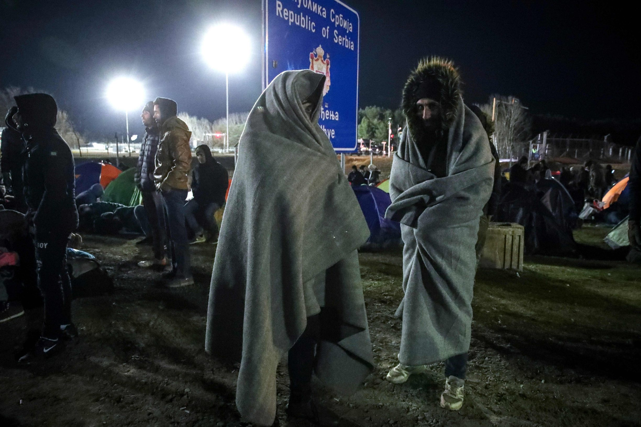 Migrants stand near the border fence at the Serbian Kelebija border village near Subotica on February 6, 2020, as the Tompa road border-crossing on the Hungarian side has been temporarily closed by the Hungarian police. - Hungarian police temporarily closed a Serbian border crossing on February 6 after a large migrant group showed up there and demanded to be let in. The attempt came a week after 60-70 people tried to get into Hungary at another Serbian border crossing under cover of night, prompting security staff to fire warning shots in the air. Hungarian police report a sharp rise in attempts to cross the country's southern borders since December. (Photo by Istvan HUSZTI / AFP)