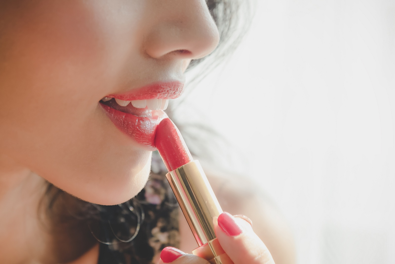 Close up beautiful luxury young woman applying lip liner to nude red lips. Close up shot and make up cosmetic of woman putting lipstick on her lip.