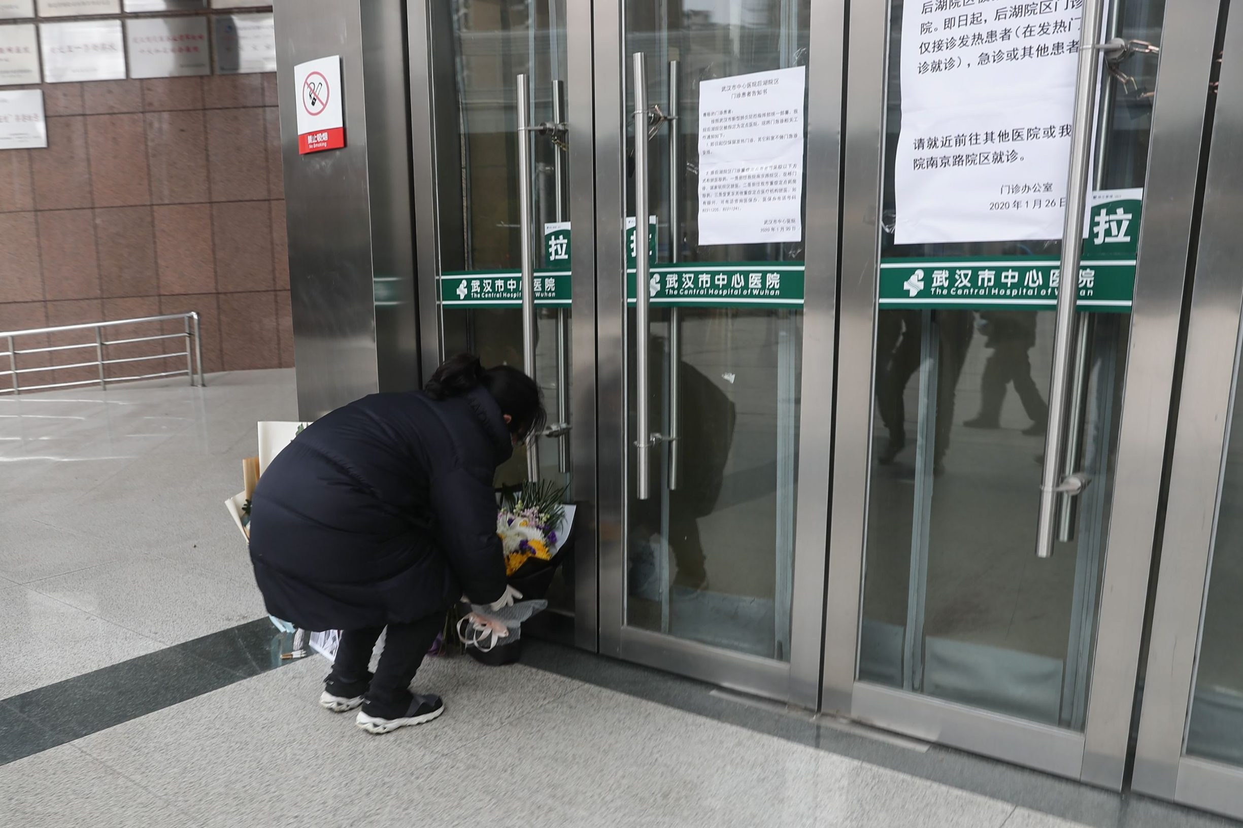 A resident places flowers for the late ophthalmologist Li Wenliang at the Houhu Branch of Wuhan Central Hospital in Wuhan in China's central Hubei province on February 7, 2020. - A Chinese doctor who was punished after raising the alarm about China's new coronavirus died from the pathogen on February 7, sparking an outpouring of grief and anger over a worsening crisis that has now killed more than 630 people. (Photo by STR / AFP) / China OUT