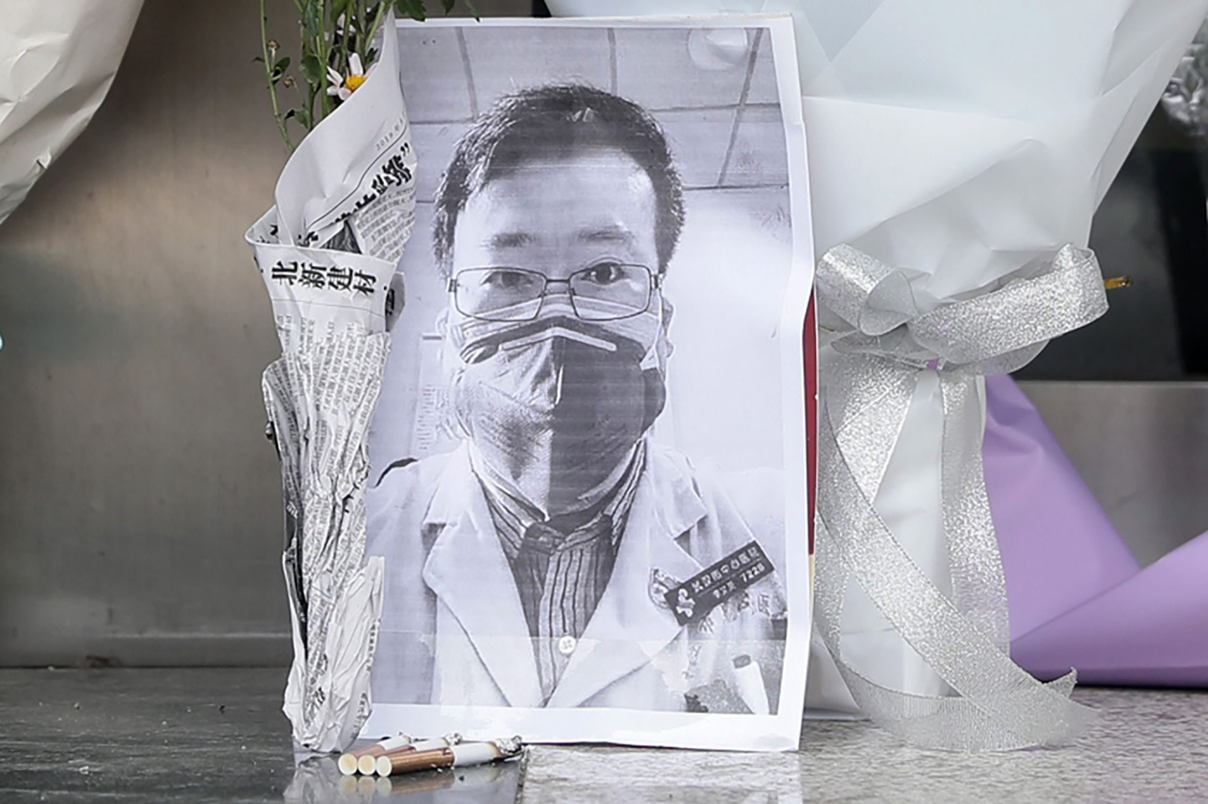 A photo of the late ophthalmologist Li Wenliang is seen with flower bouquets at the Houhu Branch of Wuhan Central Hospital in Wuhan in China's central Hubei province on February 7, 2020. - A Chinese doctor who was punished after raising the alarm about China's new coronavirus died from the pathogen on February 7, sparking an outpouring of grief and anger over a worsening crisis that has now killed more than 630 people. (Photo by STR / AFP) / China OUT