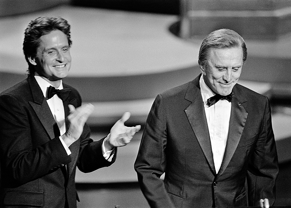 (FILES) In this file photo taken on March 25, 1985 US actor Michael Douglas (L) applauds his father US actor Kirk Douglas during the 57th Annual Academy Awards, in Hollywood, California. - US silver screen legend Kirk Douglas, the son of Jewish Russian immigrants who rose through the ranks to become one of Hollywood's biggest-ever stars, has died at 103, his family said on February 5, 2020. (Photo by ROB BOREN / AFP)