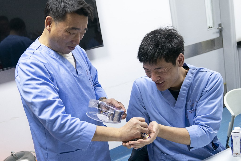 (200124) -- WUHAN, Jan. 24, 2020 (Xinhua) -- Peng Zhiyong (L), head of the department of critical care medicine of Zhongnan Hospital, hands out candies to his colleague Chen Shaofeng in the office of Zhongnan Hospital of Wuhan University in Wuhan, central China's Hubei Province, Jan. 24, 2020. About 80,000 medical workers in Wuhan will combat against the novel coronavirus (2019-nCoV) in the front line during the Chinese Lunar New Year holiday. (Xinhua/Xiong Qi)