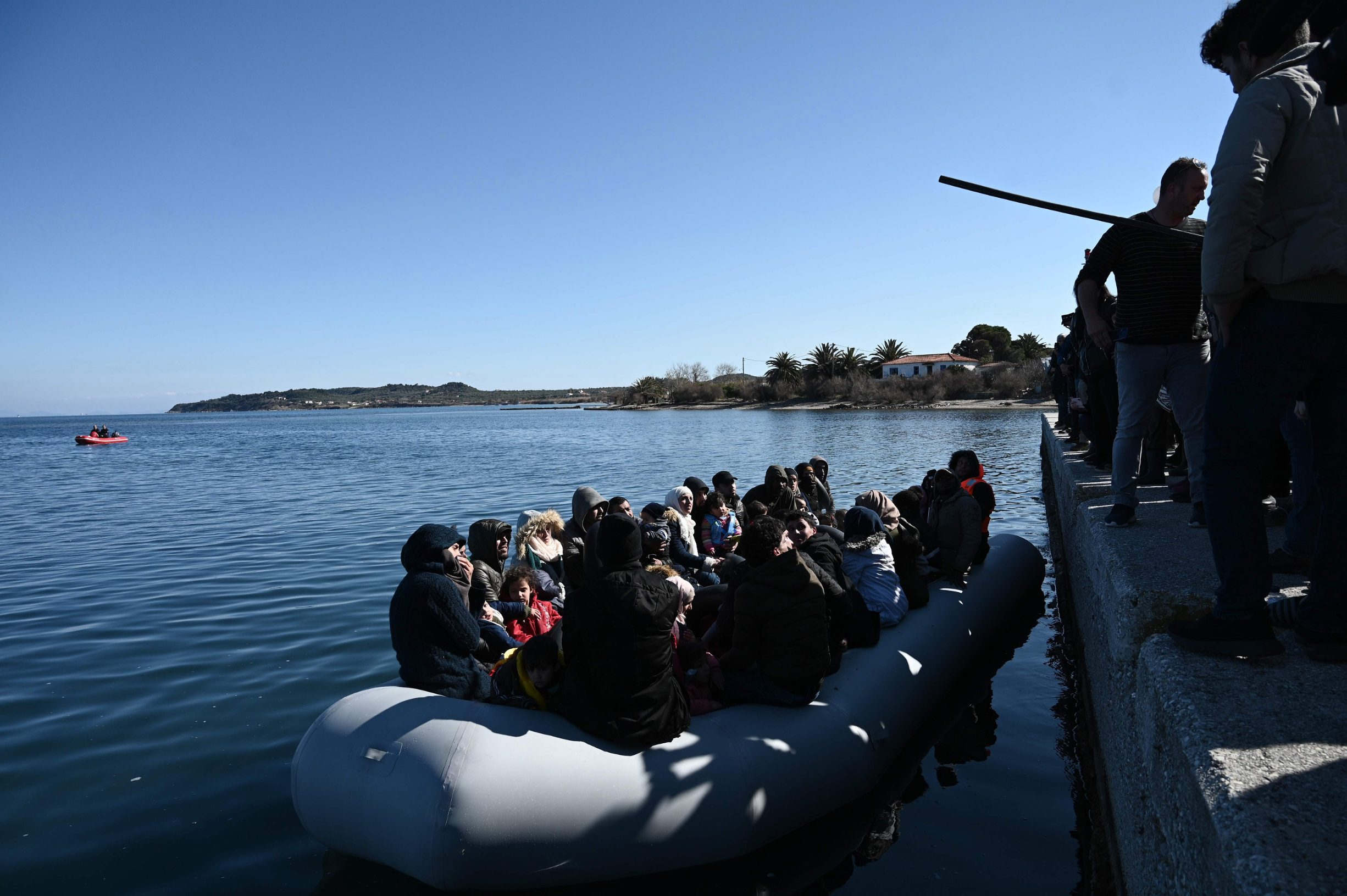 Migrants are seen on an inflatable boat as local residents prevent them from disembarking in Lesbos island, on March 1, 2020. - Greece said Sunday it has blocked nearly 10,000 migrants at its border with Turkey, which opened its gates to Europe as tensions mount over its deepening conflict in Syria.  Migrant numbers have swelled along the rugged frontier after Turkey's president Recep Tayyip Erdogan said it