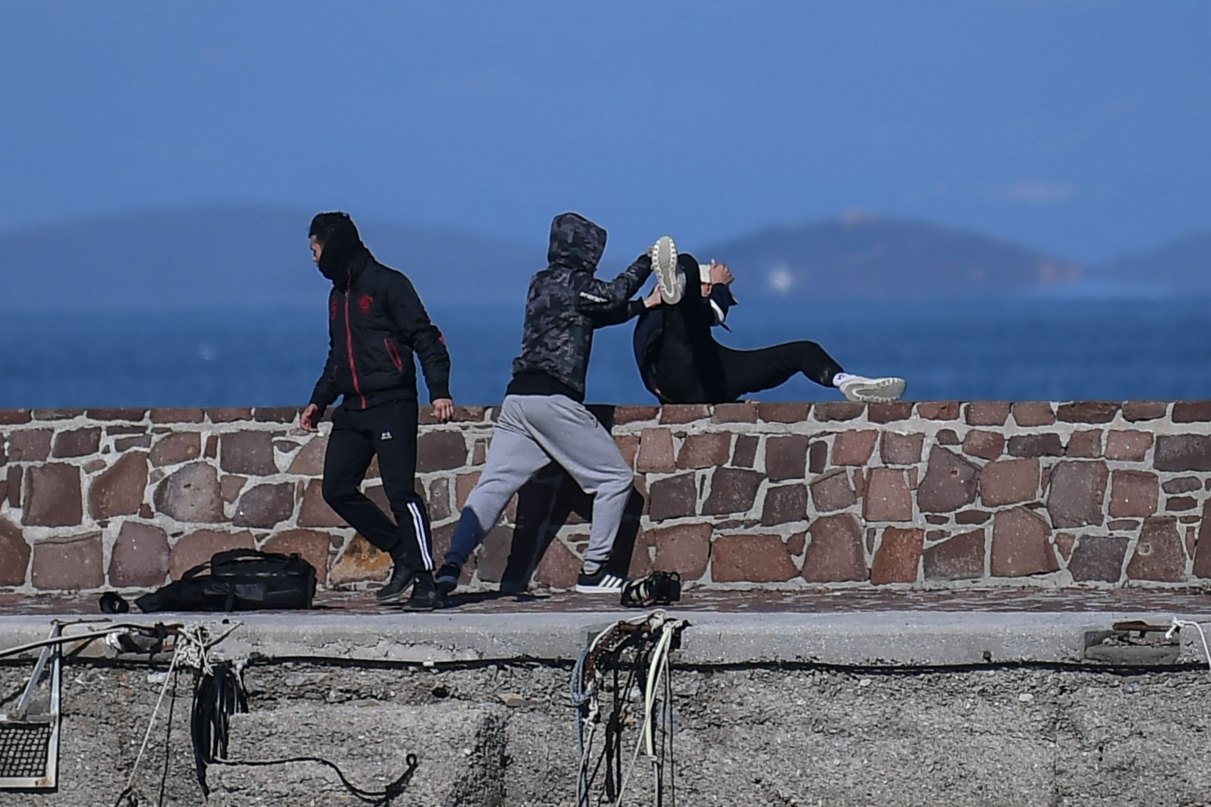 TOPSHOT - A journalist (R) is attacked by residents who are trying to prevent migrants from disembarking on the Greek island of Lesbos, on March 1, 2020. - The United Nation called on March 1 for calm and urged states to refrain from