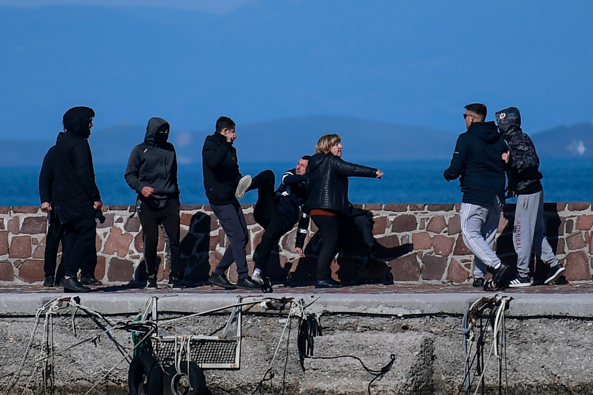 A journalist (C) receives help from a woman as he is attacked by residents who are trying to prevent migrants from disembarking on the Greek island of Lesbos, on March 1, 2020. - The United Nation called on March 1 for calm and urged states to refrain from