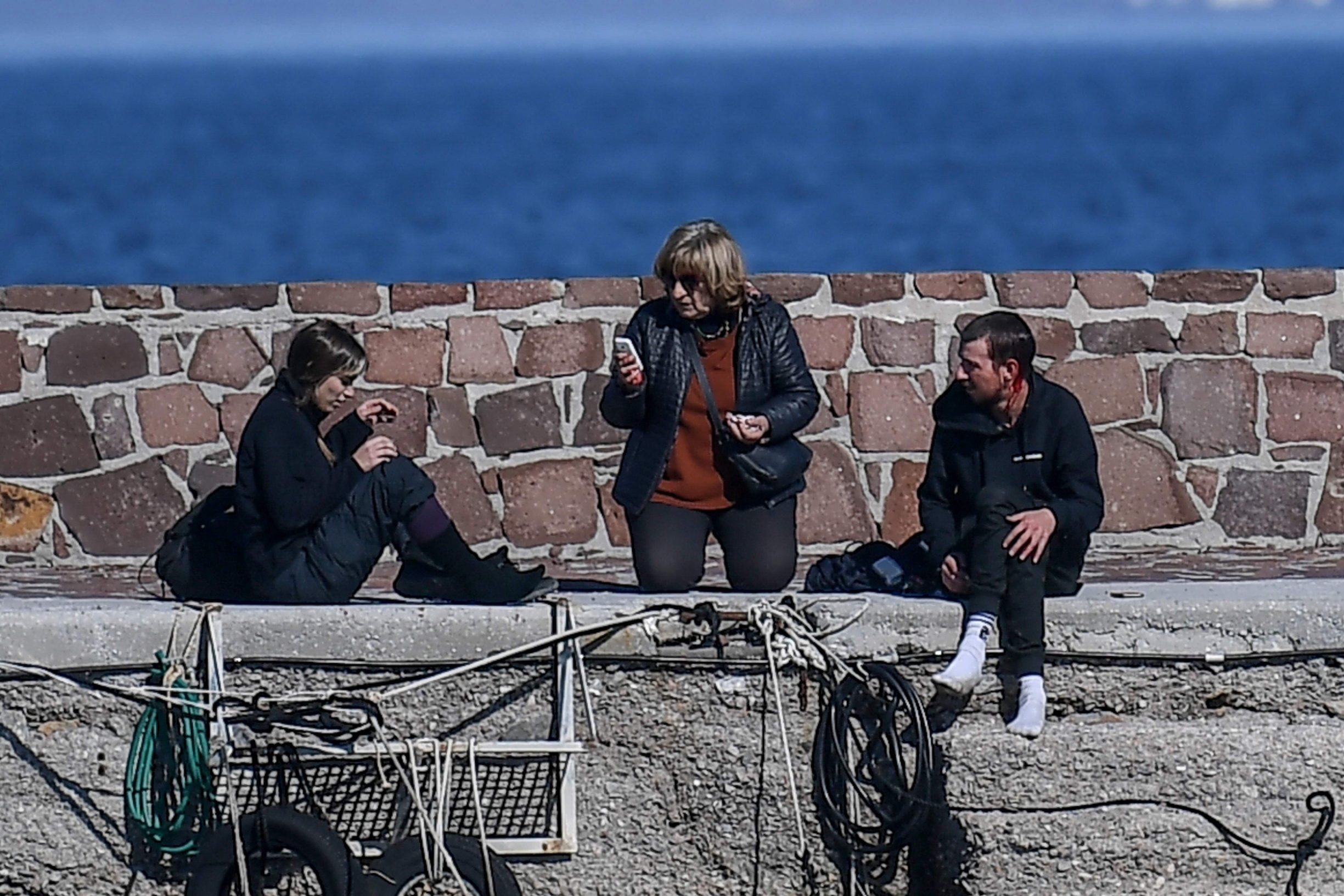 A journalist (R) receives assistance from two women after being attacked by residents who are trying to prevent migrants from disembarking on the Greek island of Lesbos, on March 1, 2020. - The United Nation called on March 1 for calm and urged states to refrain from