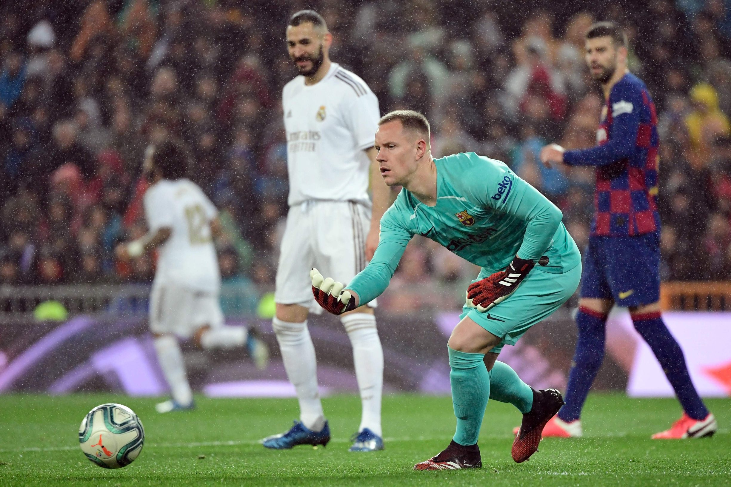 Barcelona's German goalkeeper Marc-Andre Ter Stegen hands the ball to teammates during the Spanish League football match between Real Madrid and Barcelona at the Santiago Bernabeu stadium in Madrid on March 1, 2020. (Photo by JAVIER SORIANO / AFP)