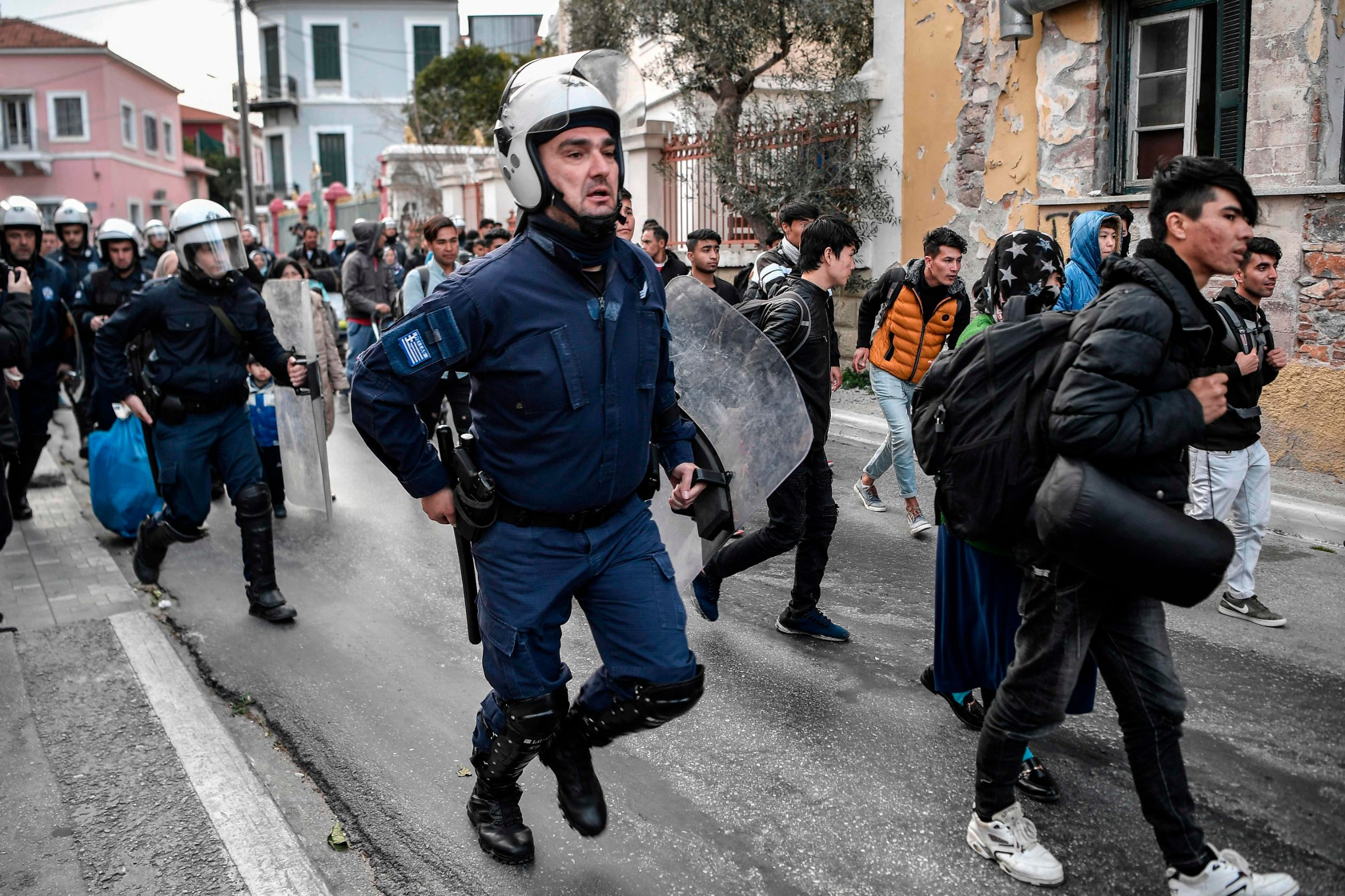 Greek anti-riot police run after migrants and refugees