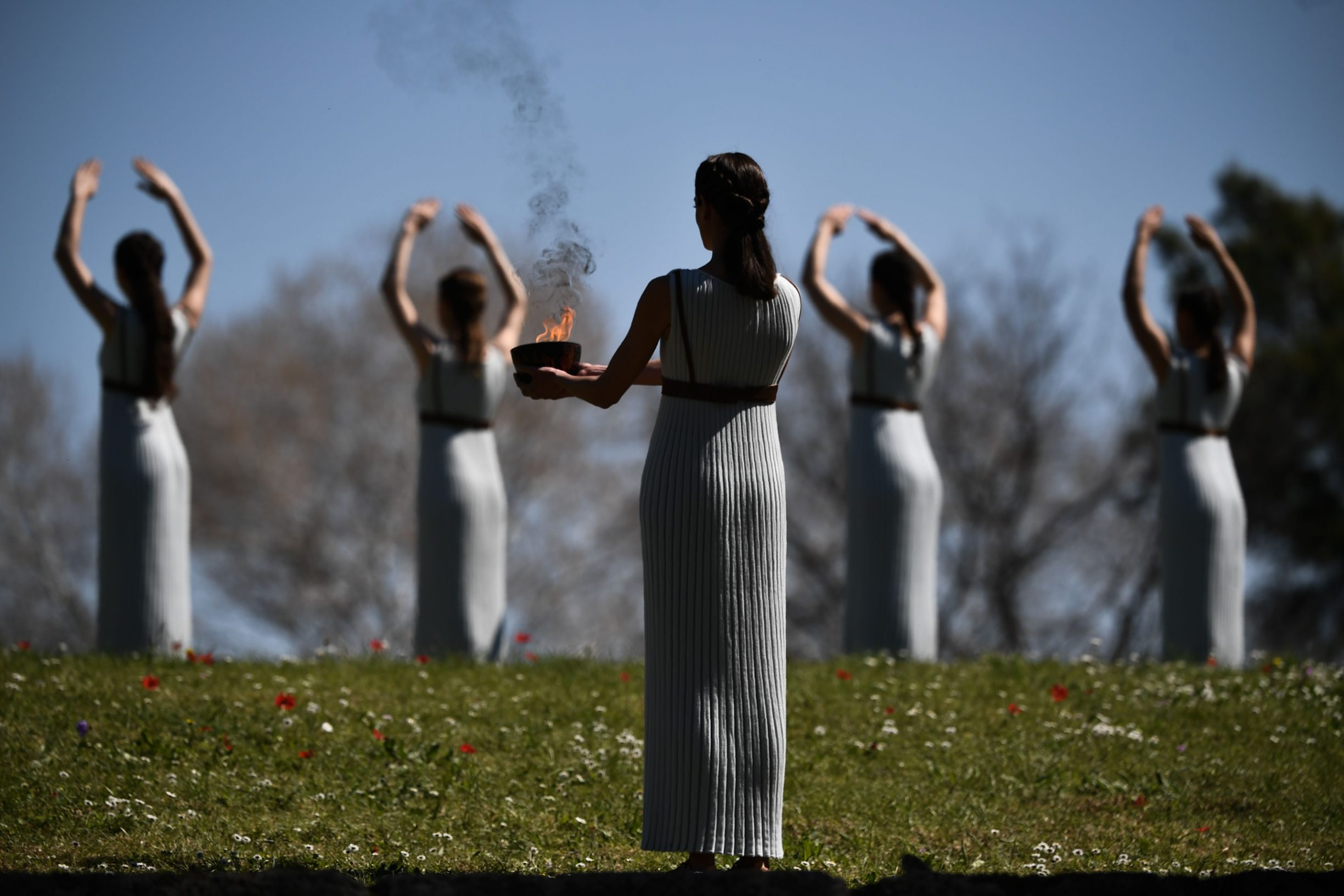 Women dressed as priestesses take part in the Olympic flame lighting ceremony in ancient Olympia, ahead of Tokyo 2020 Olympic Games on March 12, 2020. (Photo by ARIS MESSINIS / AFP)