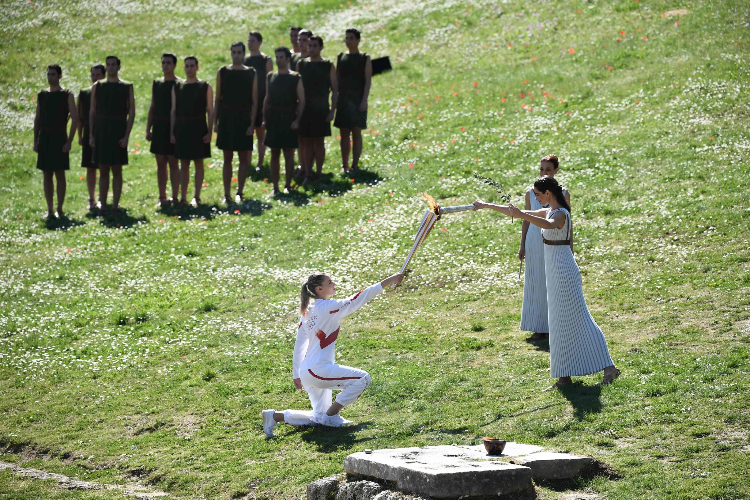 TOPSHOT - Torchbearer Greece's Anna Korakaki (L), Rio 2016 gold medallist in the 25m pistol shooting, receives the Olympic flame during the flame lighting ceremony on March 12, 2020 in ancient Olympia, ahead of the Tokyo 2020 Olympic Games. (Photo by ARIS MESSINIS / AFP)