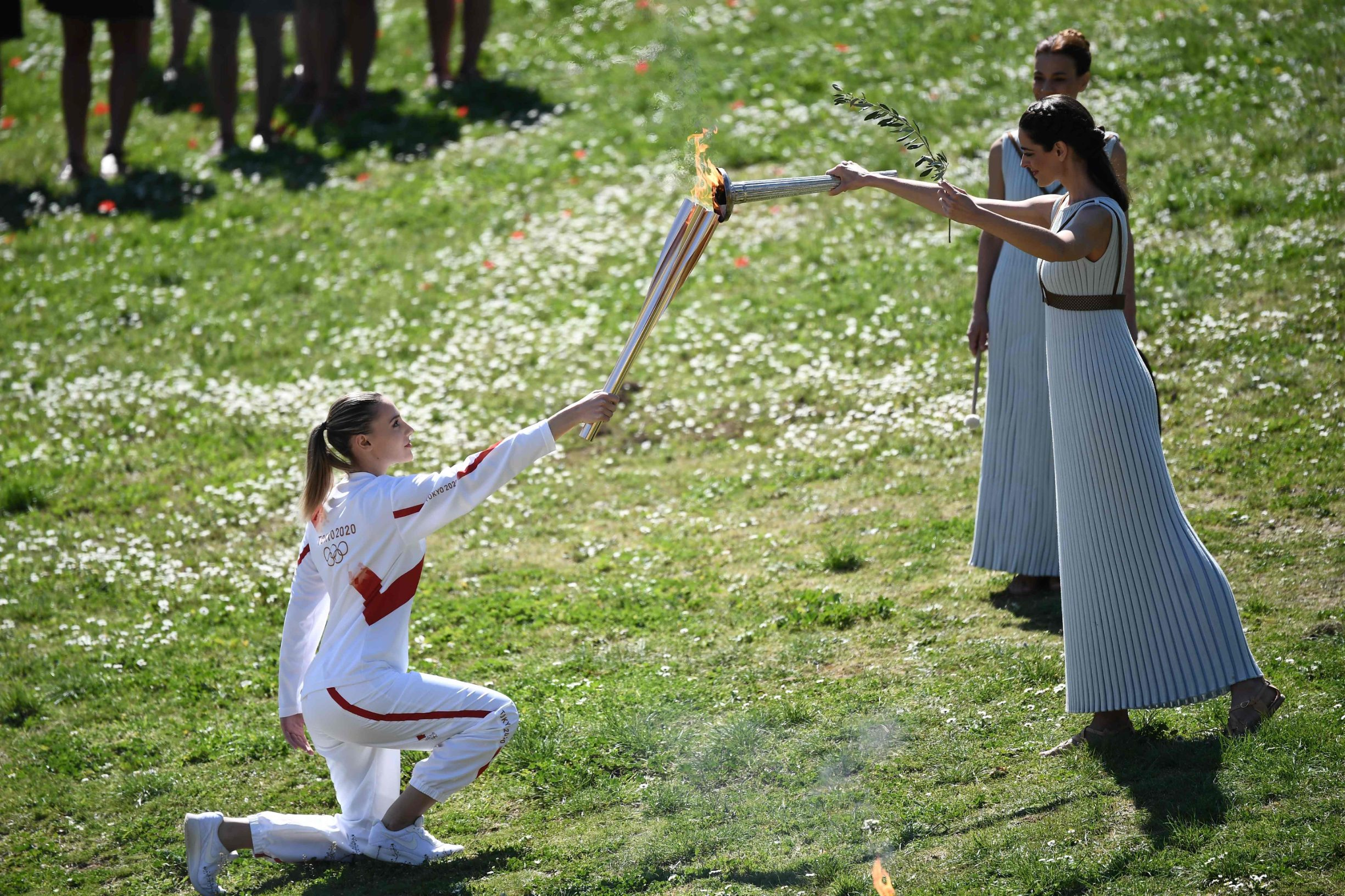 Torchbearer Greece's Anna Korakaki (L), Rio 2016 gold medallist in the 25m pistol shooting, receives the Olympic flame during the flame lighting ceremony on March 12, 2020 in ancient Olympia, ahead of the Tokyo 2020 Olympic Games. (Photo by ARIS MESSINIS / AFP)
