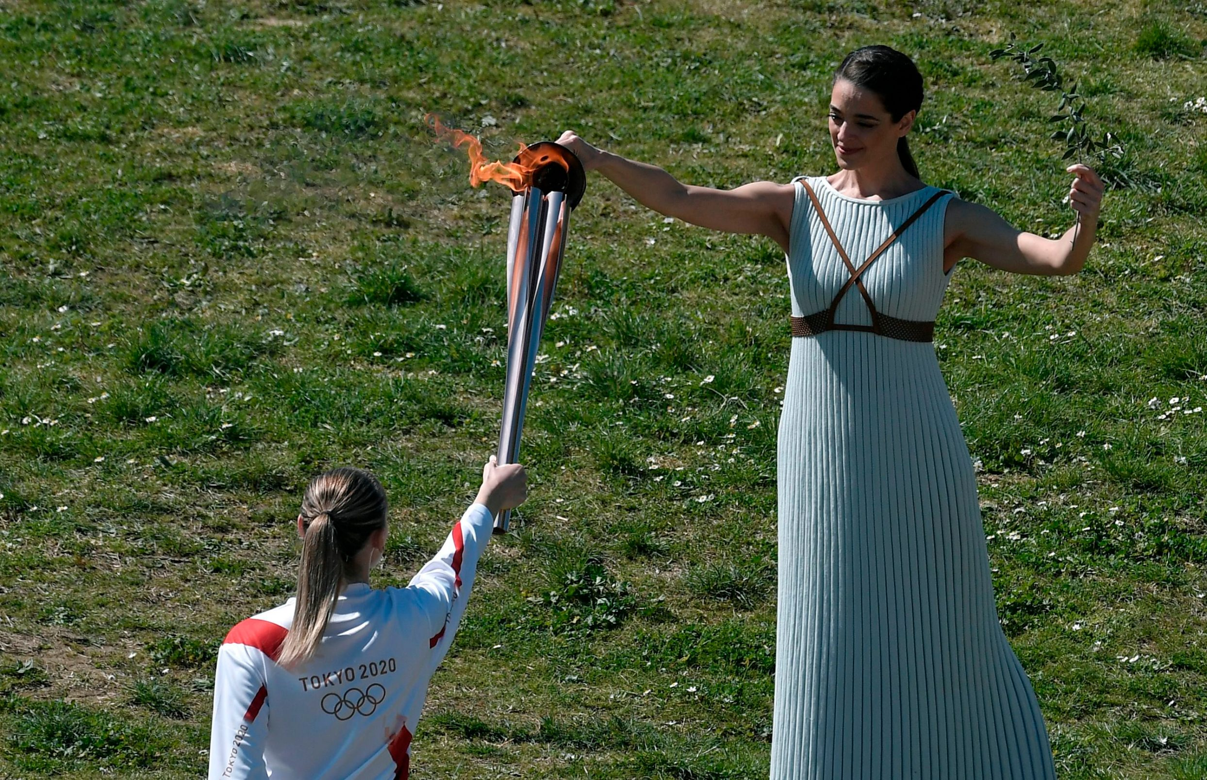 Torchbearer Greece's Anna Korakaki (back), Rio 2016 gold medallist in the 25m pistol shooting, receives the Olympic flame during the flame lighting ceremony on March 12, 2020 in ancient Olympia, ahead of the Tokyo 2020 Olympic Games. (Photo by LOUISA GOULIAMAKI / AFP)