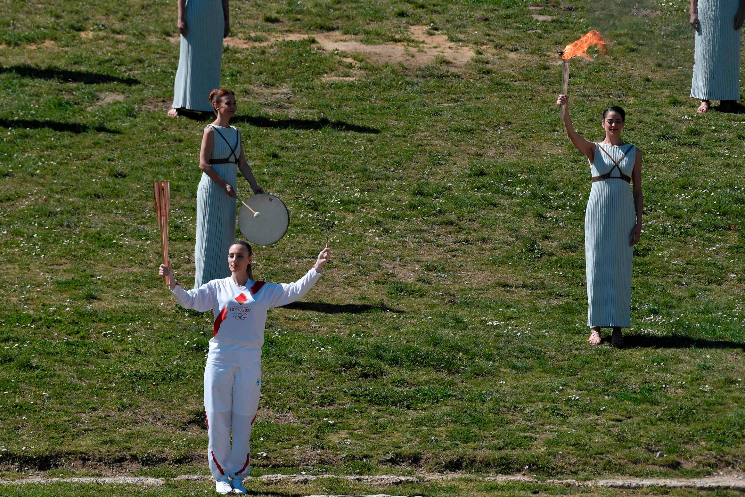 Greece's Anna Korakaki (L), Rio 2016 gold medallist in the 25m pistol shooting, torchbearer, holds the Olympic flame during the flame lighting ceremony on March 12, 2020 in ancient Olympia, ahead of the Tokyo 2020 Olympic Games. (Photo by LOUISA GOULIAMAKI / AFP)