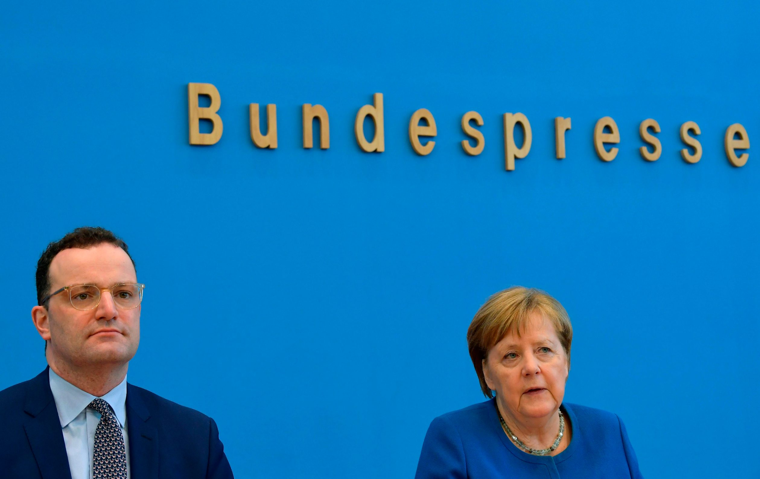 German Health Minister Jens Spahn (L) and German Chancellor Angela Merkel give a press conference on March 11, 2020 in Berlin to comment on the situation of the spread of the novel coronavirus in the country. (Photo by Tobias SCHWARZ / AFP)