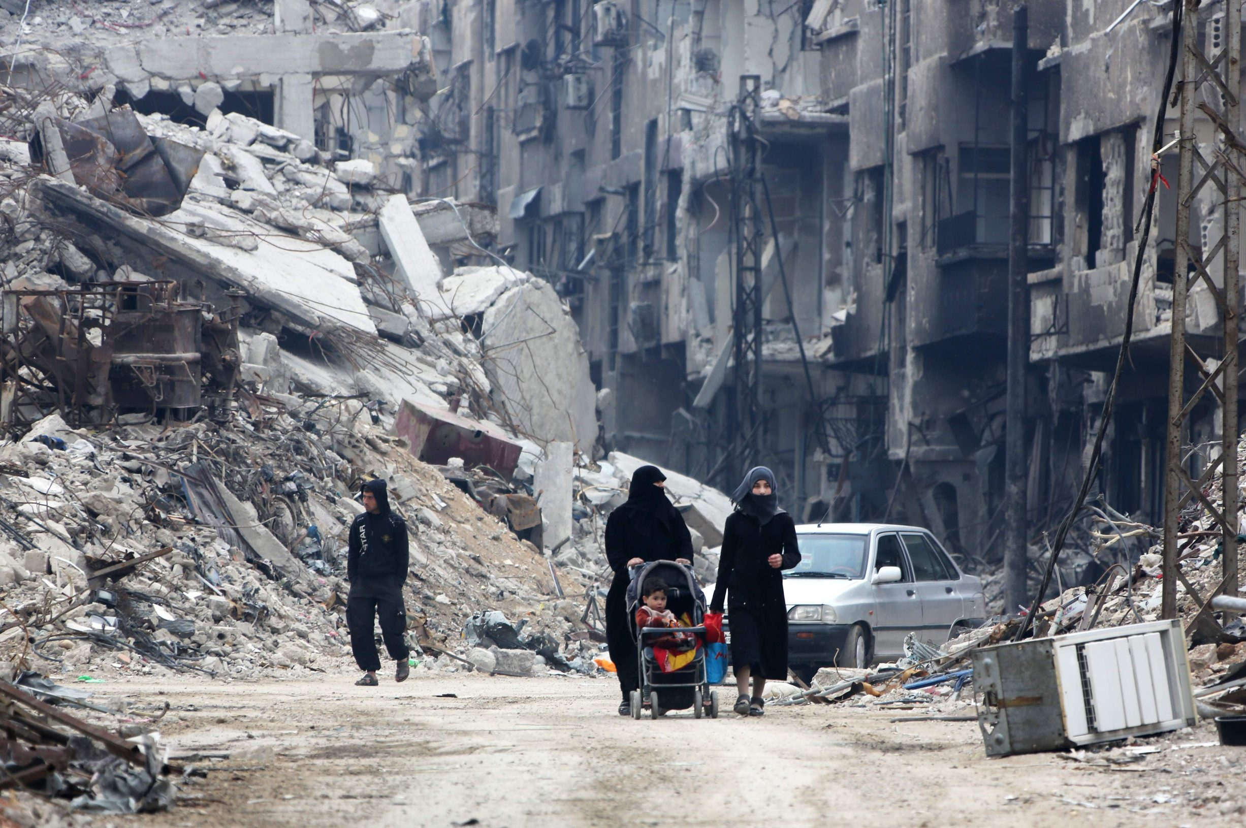 (FILES) In this file photo taken on March 30, 2018 Civilians walk along a destroyed street in the former rebel-held town of Harasta in Eastern Ghouta, a week after regime forces retook the town from the rebels. - As it enters its tenth year, the war in Syria is anything but abating as foreign powers scrap over a ravaged country where human suffering keeps reaching new levels. (Photo by STRINGER / AFP)