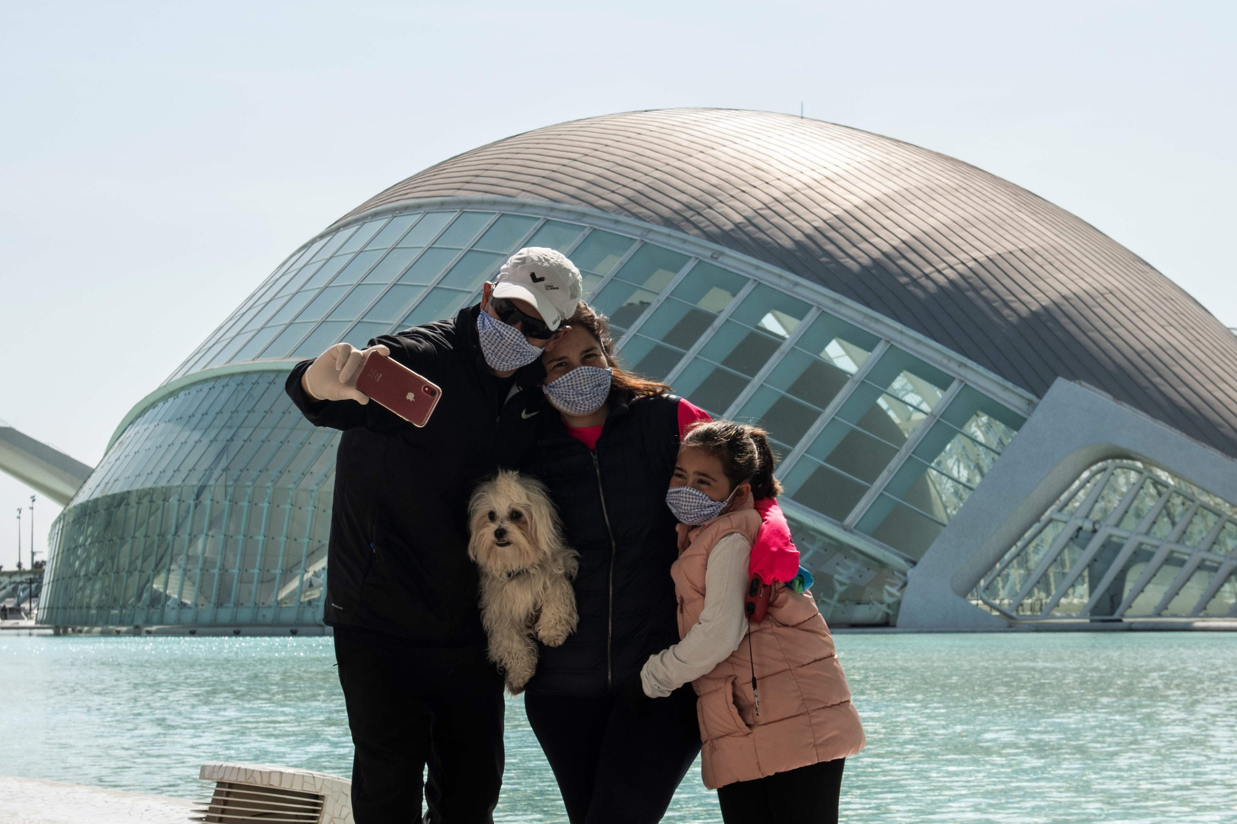A family wearing protective masks take a selfie at the City of Arts and Sciences in Valencia on March 14, 2020 as Spain confirmed more than 1,500 new cases of coronavirus between Friday and Saturday raising its total to 5,753 cases, the second-highest number in Europe after Italy.