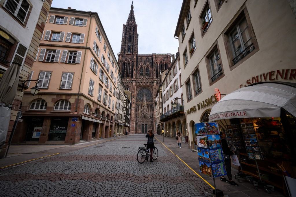 A woman rides a bike in a street near the Cathedral in Strasbourg, eastern France, on March 17, 2020, a few hours before the order of staying at home to all French citizens comes into effect, in order to avoid the spreading of the novel coronavirus. - French President asked people to stay at home to avoid the spreading the Covid-19, saying only necessary trips would be allowed and violations would be punished. The country has already shut cafes, restaurants, schools and universities and urged people to limit their movements. (Photo by PATRICK HERTZOG / AFP)