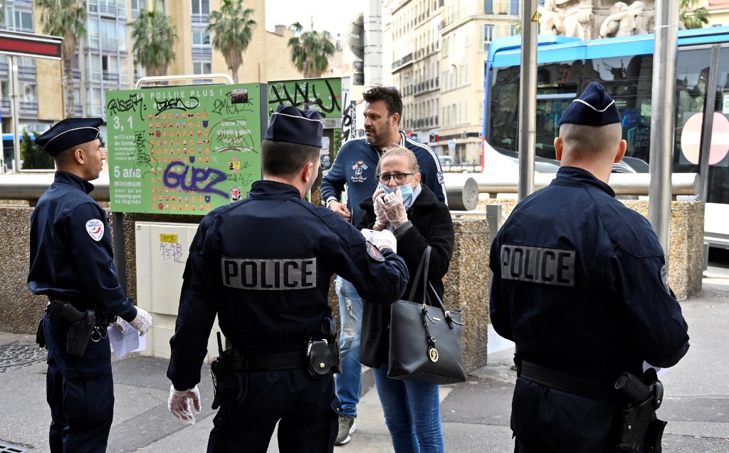 A woman wearing a facemask for protective measures, speaks to French police officers patroling and controling citizens, at the place Castellane, in Marseille, southern France on March on 17, 2020 while a strick lockdown comes into in effect to stop the spread of the COVID-19 in the country. - A strict lockdown requiring most people in France to remain at home came into effect at midday on March 17, 2020, prohibiting all but essential outings in a bid to curb the coronavirus spread. The government has said tens of thousands of police will be patrolling streets and issuing fines of 38 to 135 euros (-0) for people without a written declaration justifying their reasons for being out. (Photo by GERARD JULIEN / AFP)