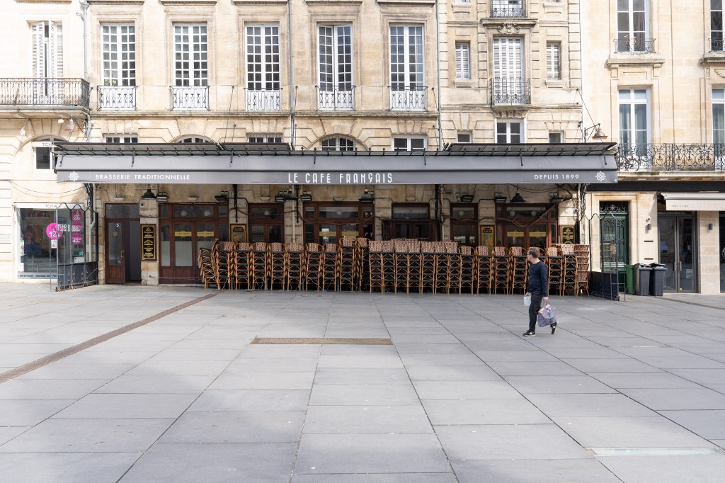 A man walks home from the grocery store and walks past a closed restaurant in the street before confinement. Containment was declared this Tuesday, March 17, 2020 at 12:00 noon. Bordeaux. 17. March 2020. Un homme rentre de l'�picerie et passe devant un restaurant ferm� dans la rue avant le confinement . Le confinement a ete declare ce mardi 17 mars 2020 a 12h. Bordeaux. 17 Mars 2020.