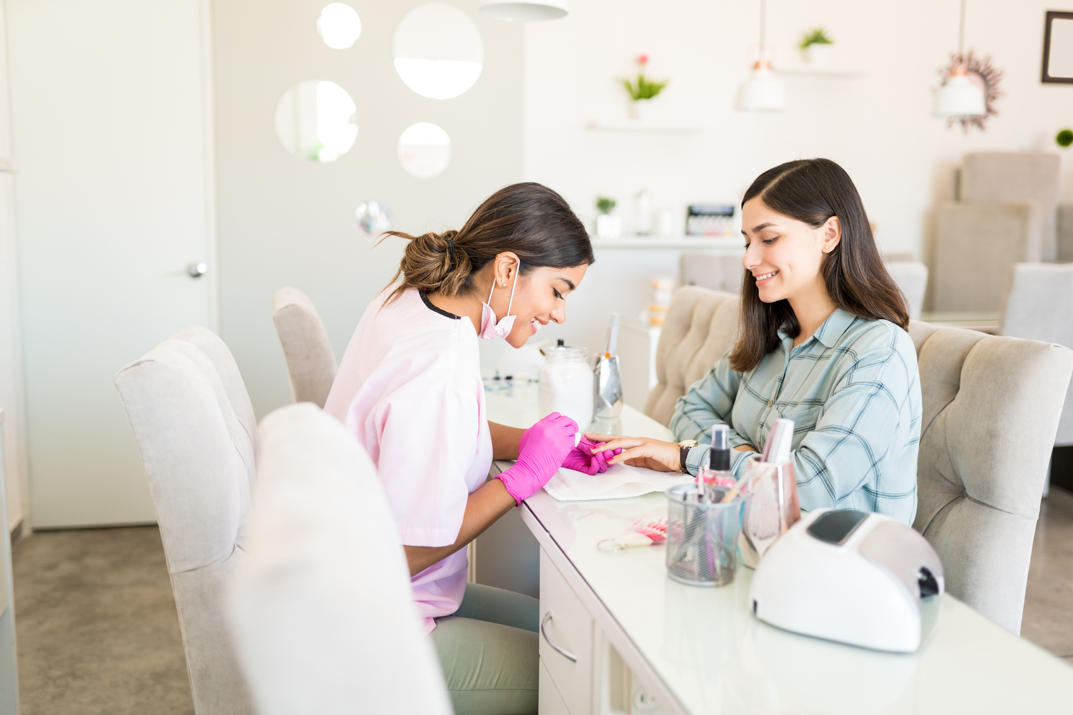 Smiling manicurist decorating nails with color on client's hand at beauty spa