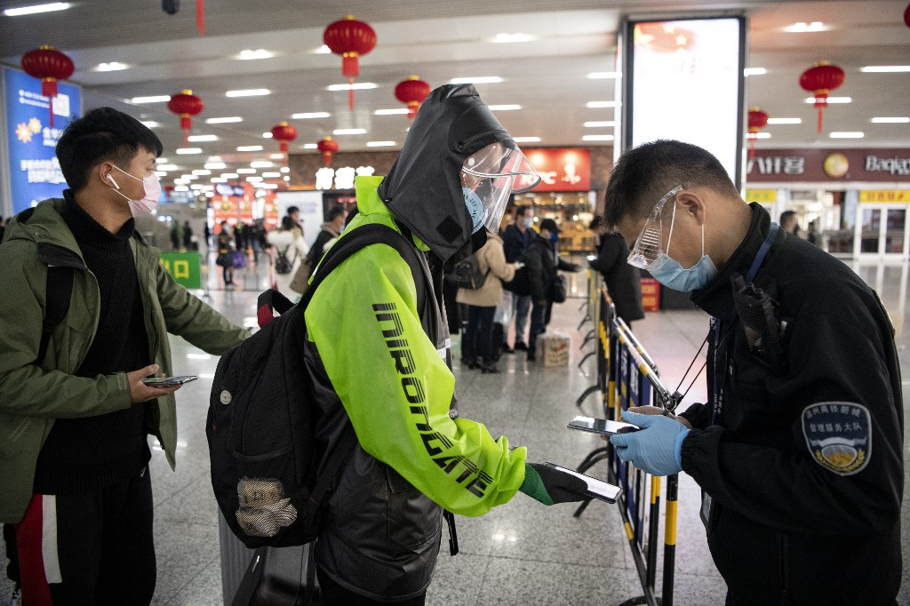 This photo taken on February 28, 2020 shows a passenger wearing a face mask as he shows a green QR code on his phone to show his health status to security upon arrival at Wenzhou railway station in Wenzhou. - The National Health Commission on March 1 reported 573 new infections, bringing the total number of cases in mainland China to 79,824. (Photo by NOEL CELIS / AFP)