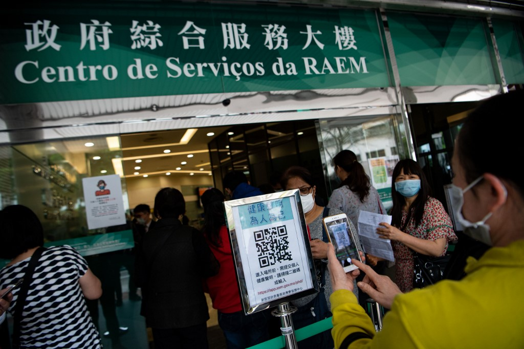 (200302) -- MACAO, March 2, 2020 (Xinhua) -- People scan QR code to fill in health document before entering a government service hall in Macao, south China, March 2, 2020. (Xinhua/Cheong Kam Ka)