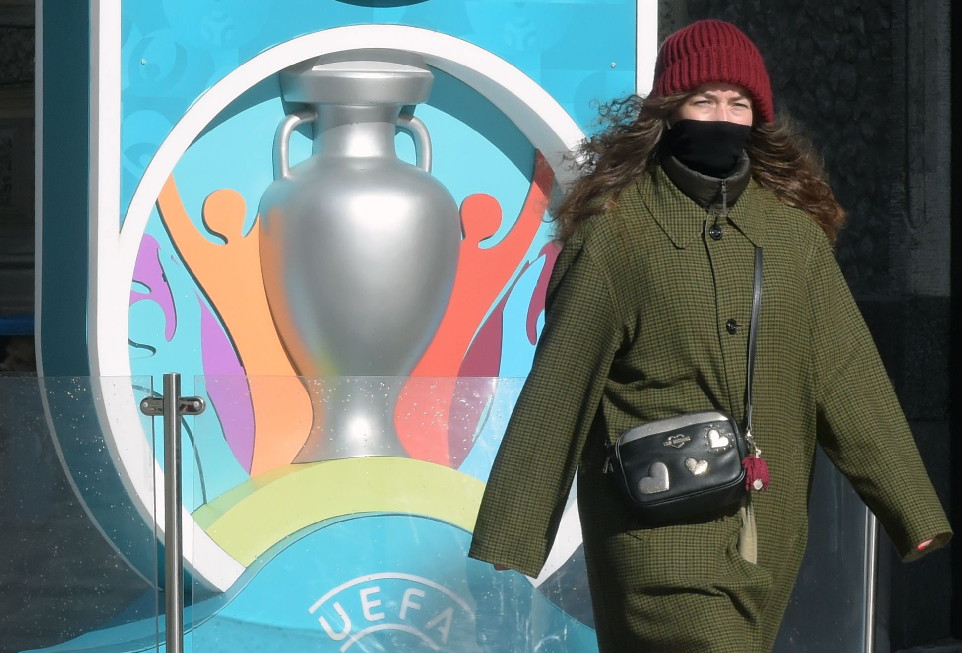 A woman wearing her scarf wrapped around her face walks past the Euro 2020 countdown clock - displaying 449 days left before the event - in downtown Saint Petersburg on March 19, 2020. - The European Championship, due to be played in June and July this year, has been postponed until 2021 because of the coronavirus pandemic, European football's governing body UEFA said on March 17, 2020. UEFA announced that the new proposed dates for the tournament were June 11 to July 11 next year, as Euro 2020 becomes Euro 2021. (Photo by OLGA MALTSEVA / AFP)