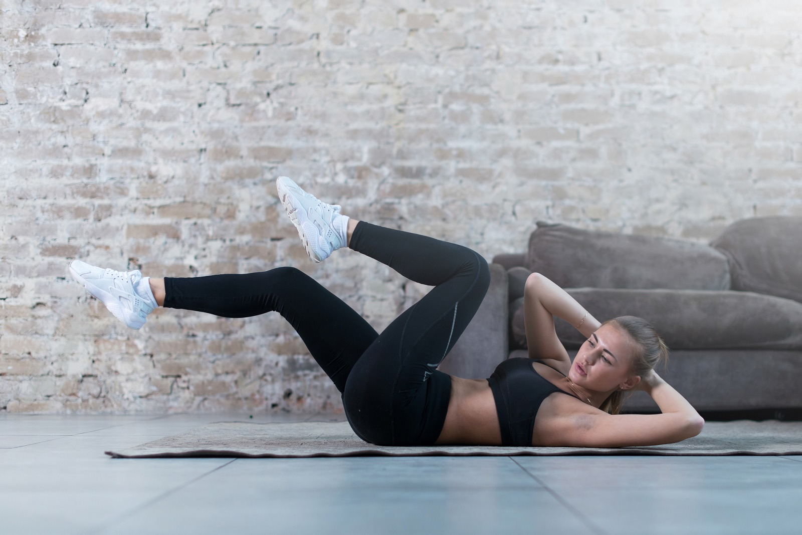 Sportive young lady doing crisscross crunch exercise lying on a rug at modern studio.