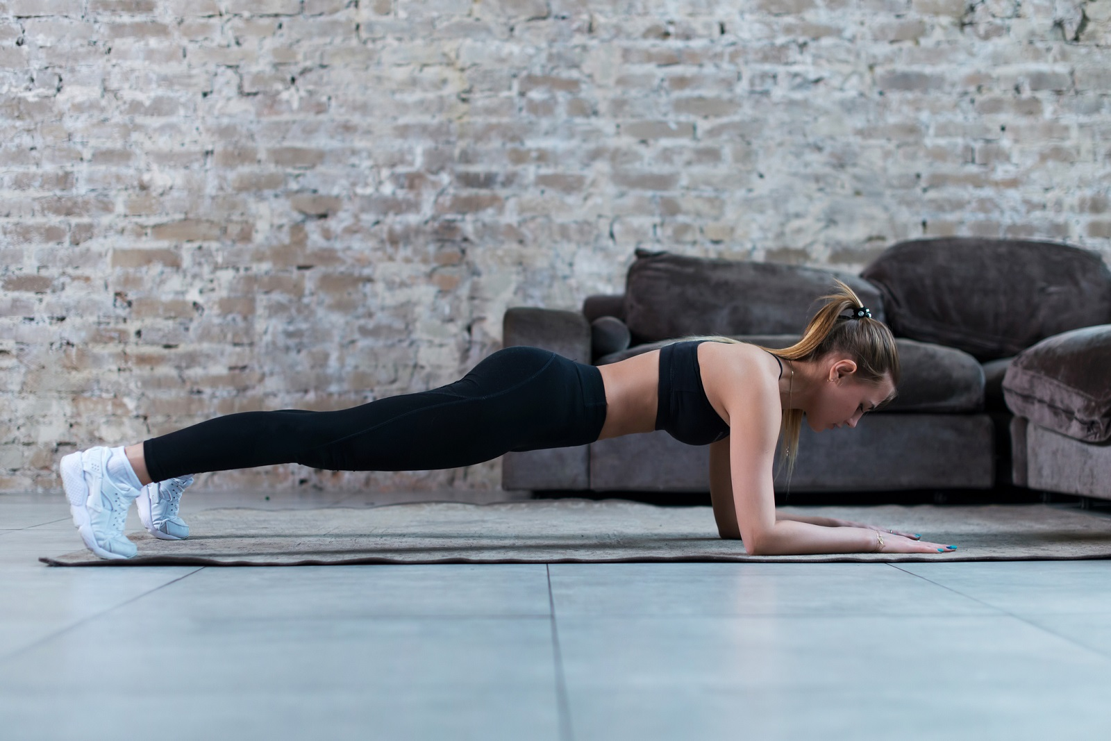 Slim young brunette wearing black gym clothing doing abdominal bridge or front plank exercise in loft apartment