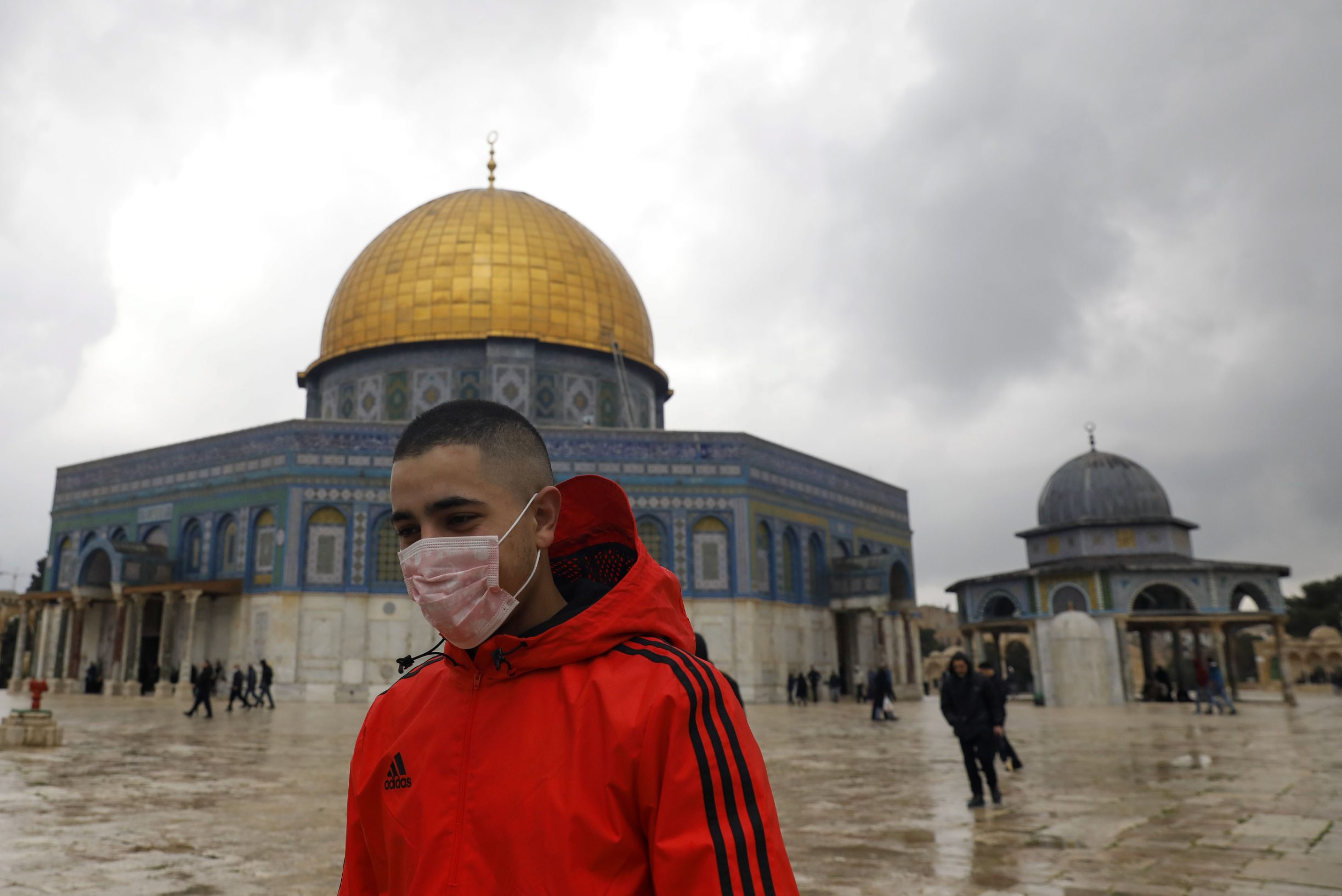 (FILES) In this file photo taken on March 06, 2020 A young man wearing a protective mask as a measure of protection against the coronavirus COVID-19, walks in front of the Dome of the Rock mosque inside the al-Aqsa compound in the Old City of Jerusalem, ahead of the Friday prayers, on March 6, 2020. - The Jerusalem Al-Aqsa mosque compound will be closed to the public from March 23, the religious authority that administers Muslim holy sites in the city announced in a rare move aimed at combatting the novel coronavirus. In a statement, the Jordan Waqf said it would