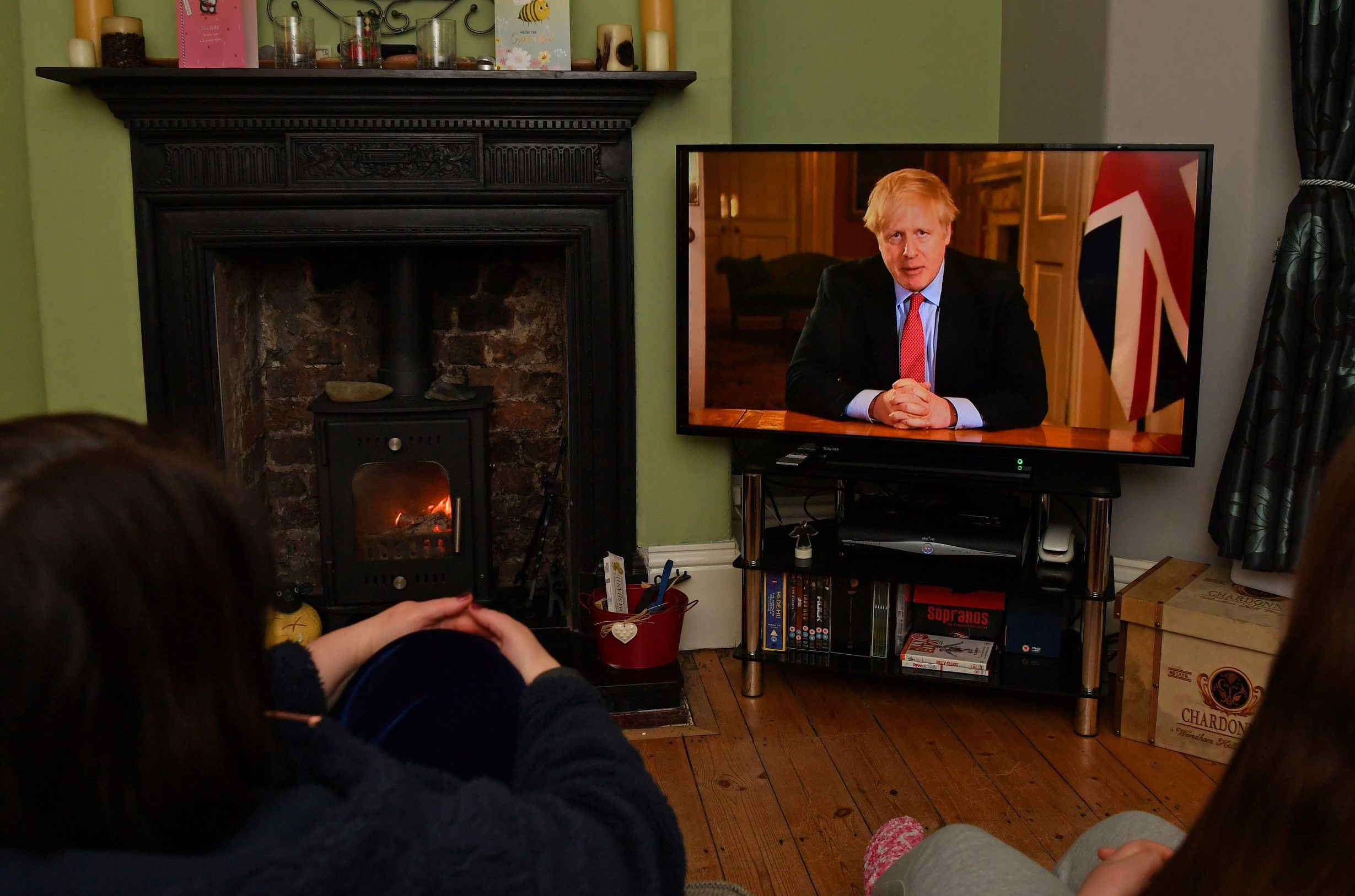 Members of a family listen as Britain's Prime Minister Boris Johnson makes a televised address to the nation from inside 10 Downing Street in London, with the latest instructions to stay at home to help contain the Covid-19 pandemic, from a house in Liverpool, north west England on March 23, 2020. - Britain on Monday ordered a three-week lockdown to tackle the spread of coronavirus, shutting