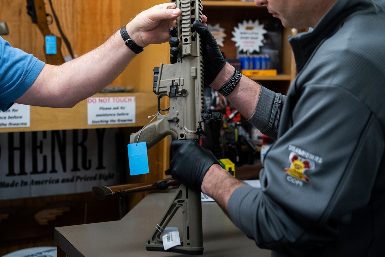 Mar 20, 2020; Glassboro, NJ, USA;  Charles N., right, who declined to provide his last name, holds a SIG516 rifle for sale inside Bob's Little Gun Shop Friday, March 20, 2020 in Glassboro, N.J. Charles, concerned over recent events surrounding COVID19, purchased a rifle and a shotgun with the idea of protecting his family.