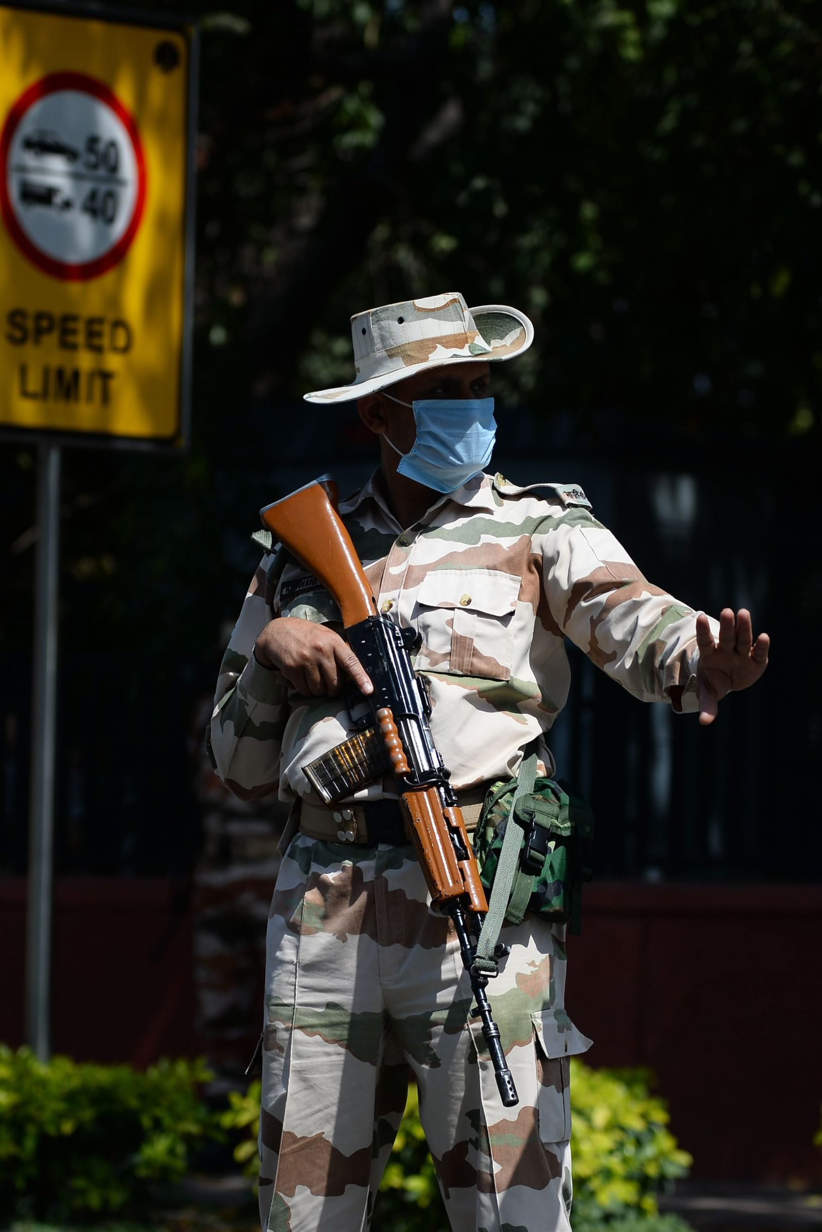 A security personnel wearing a facemask gestures to stop a motorists at a roadblock during the first day of a 21-day government-imposed nationwide lockdown as a preventive measure against the COVID-19 coronavirus in New Delhi on March 25, 2020. - India's billion-plus population went into a three-week lockdown on March 25, with a third of the world now under orders to stay indoors, as the coronavirus pandemic forced Japan to postpone the Olympics until next year. (Photo by Sajjad HUSSAIN / AFP)