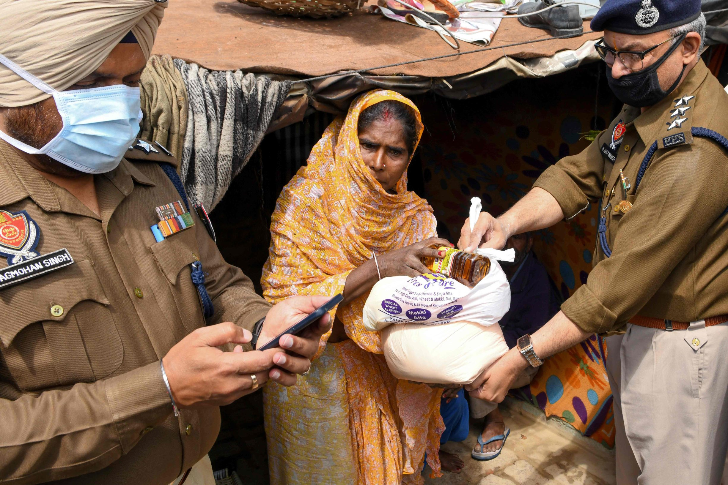 Police personnel distribute free food to people in need during the first day of a 21-day government-imposed nationwide lockdown as a preventive measure against the COVID-19 coronavirus, in Amritsar on March 25, 2020. (Photo by NARINDER NANU / AFP)