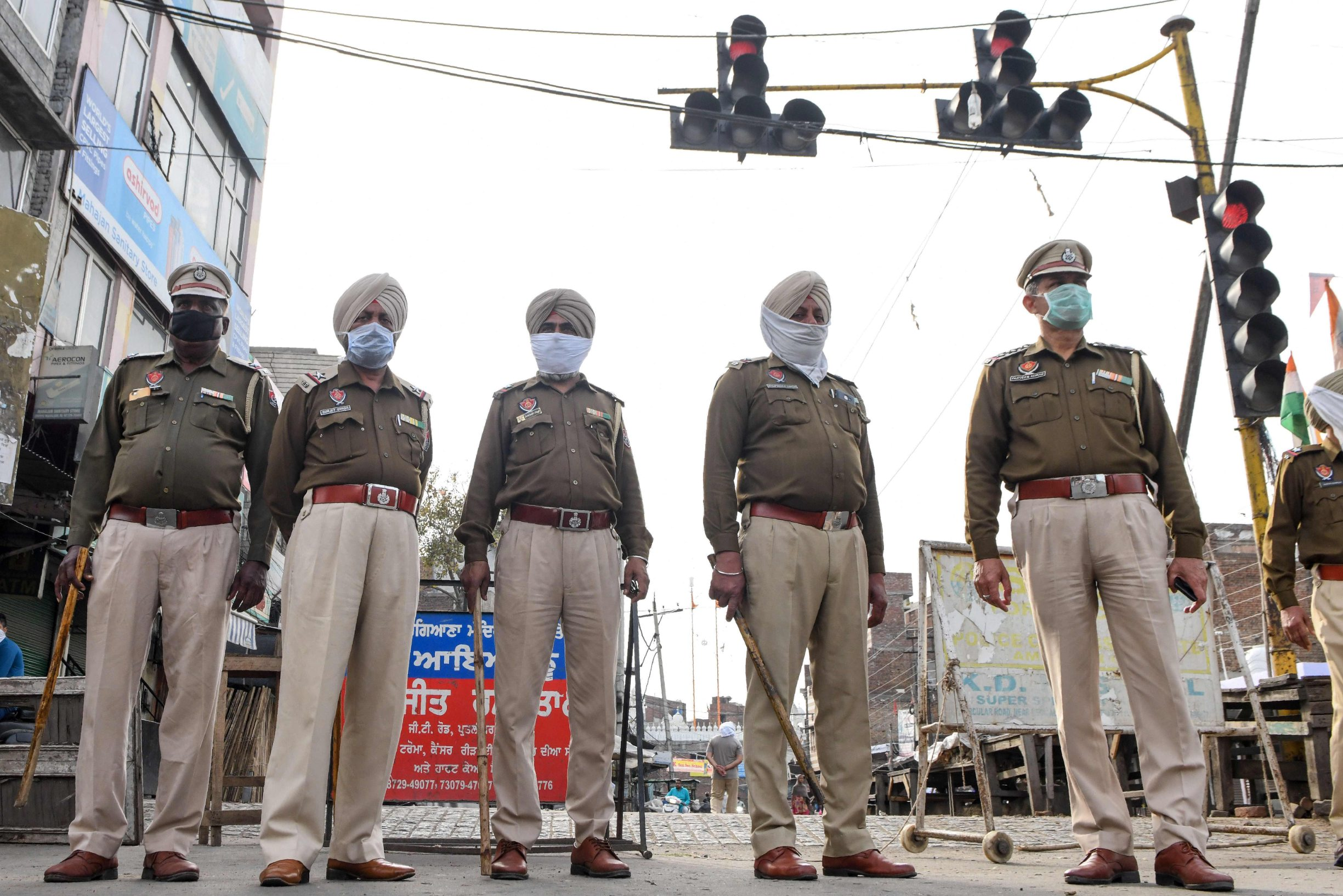 Police personnel stand guard at a traffic light during the first day of a 21-day government-imposed nationwide lockdown as a preventive measure against the COVID-19 coronavirus, in Amritsar on March 25, 2020. (Photo by NARINDER NANU / AFP)
