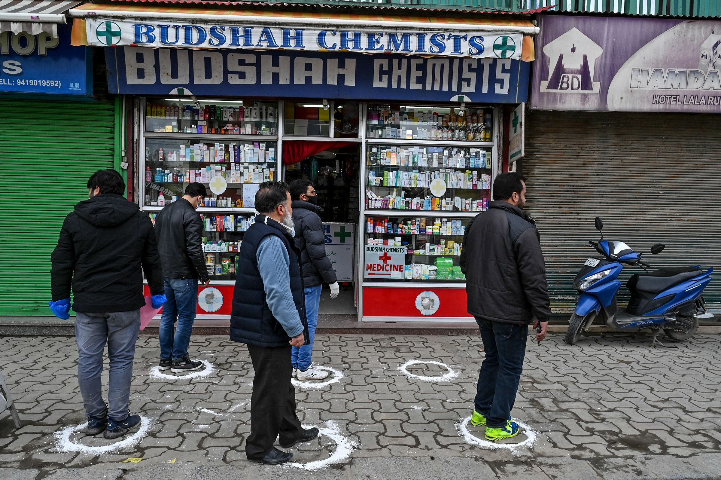 People stand on designated areas to maintain social distancing as they queue outside a medical store during a government-imposed nationwide lockdown as a preventive measure against the COVID-19 coronavirus in Srinagar on March 26, 2020. (Photo by Tauseef MUSTAFA / AFP)