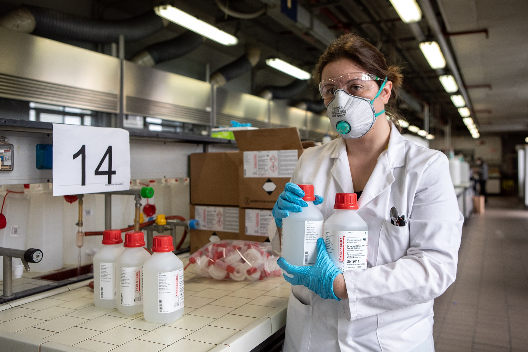 MILAN, ITALY - MARCH 19: A postdoctoral researcher, wearing gloves and a protective face mask, holds two bottles of hydrogen peroxide as she works inside the laboratory of Chemistry, Materials and Chemical Engineering 'Giulio Natta' at Politecnico di Milano on March 19, 2020 in Milan, Italy. Following the national shortage of hand sanitiser products due to the novel Coronavirus outbreak, Italy's largest technical university the Politecnico di Milano has started producing hand sanitiser to be delivered to the Protezione Civile, the Italian body dealing with the management of emergency events. The Italian government continues to enforce the nationwide lockdown measures to control the spread of COVID-19. (Photo by Emanuele Cremaschi/Getty Images)