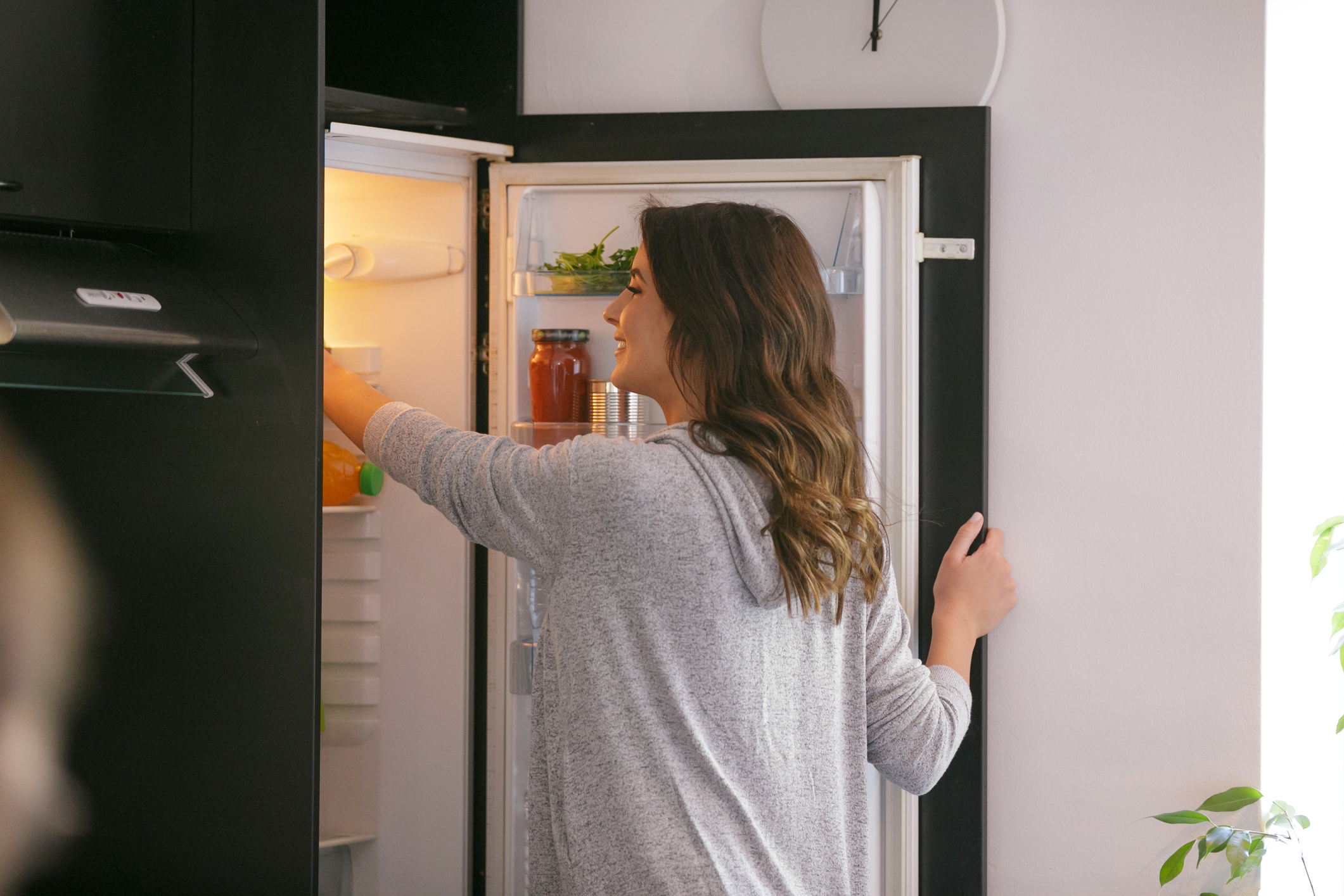 Happy woman opening the fridge and taking food from the upper shelf