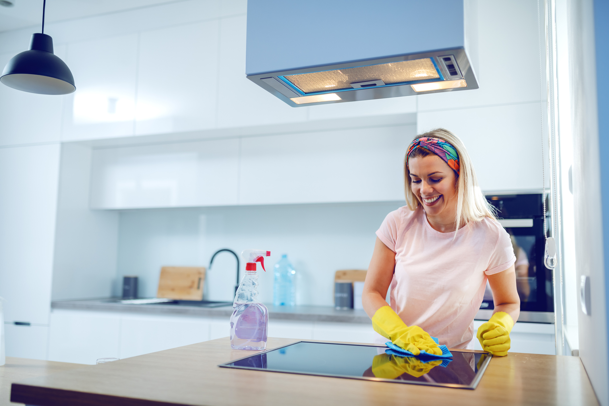 Worthy cheerful caucasian blond housewife with rubber gloves on hands cleaning stove. Kitchen interior.