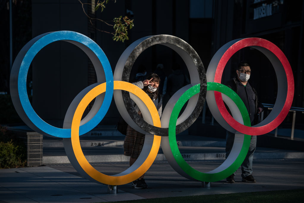 TOKYO, JAPAN - MARCH 24: People wearing face masks pose for photographs next to Olympic Rings on March 24, 2020 in Tokyo, Japan. Although an official decision is yet to be announced, International Olympic Committee member Dick Pound has said the Tokyo 2020 Olympic Games will be postponed by one year because of the Covid-19 coronavirus after the chairman of the British Olympic Association said Great Britain would be unlikely to send a team to Tokyo this summer while Australia and Canada also said they will not compete as the global Covid-19 coronavirus pandemic that has so far seen over 380,000 infections around the world forces countries to take drastic measures to protect their populations. (Photo by Carl Court/Getty Images)