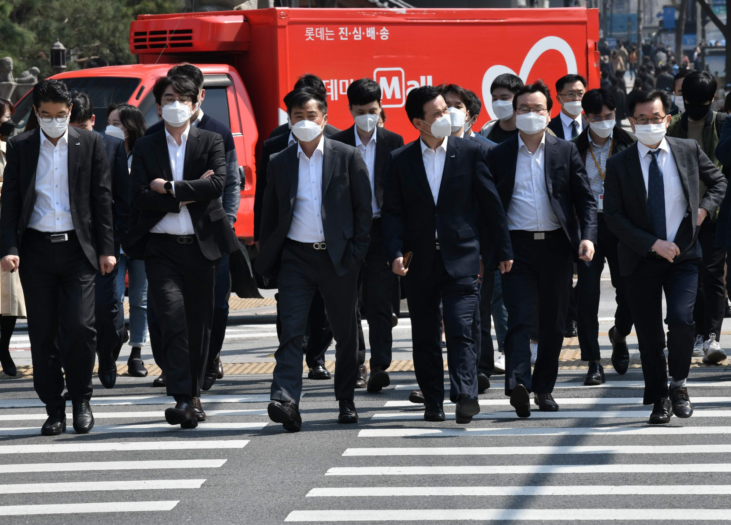 People wearing face masks cross the road in downtown Seoul on March 25, 2020. (Photo by Jung Yeon-je / AFP)
