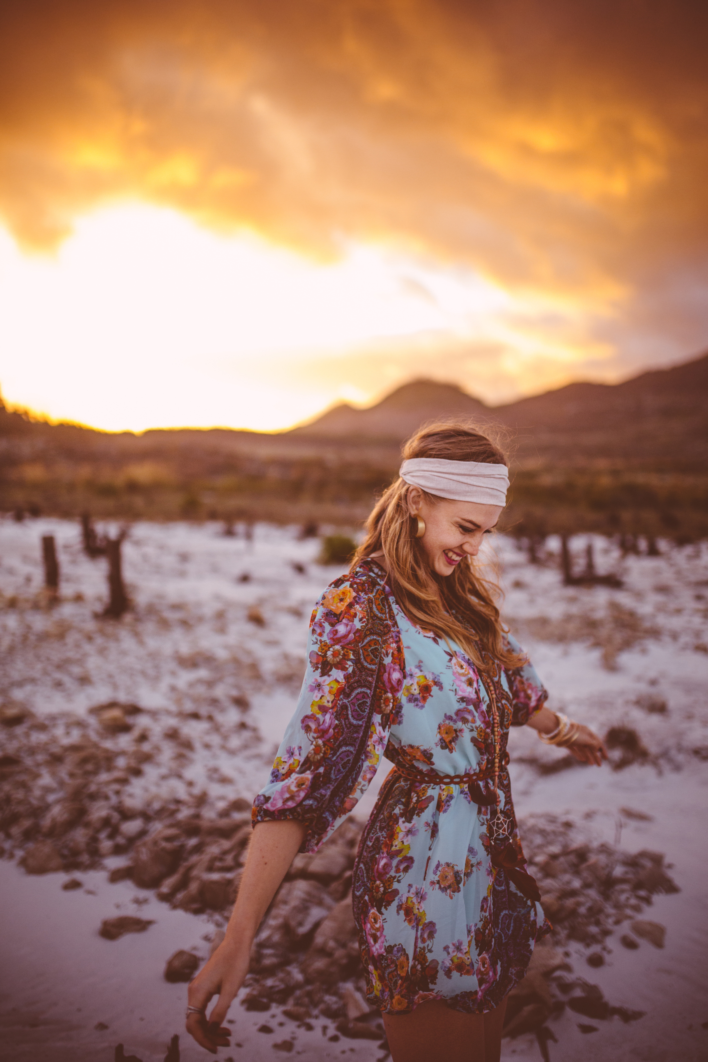 Candid shot of a boho girl walking happily in nature on a peaceful summer evening
