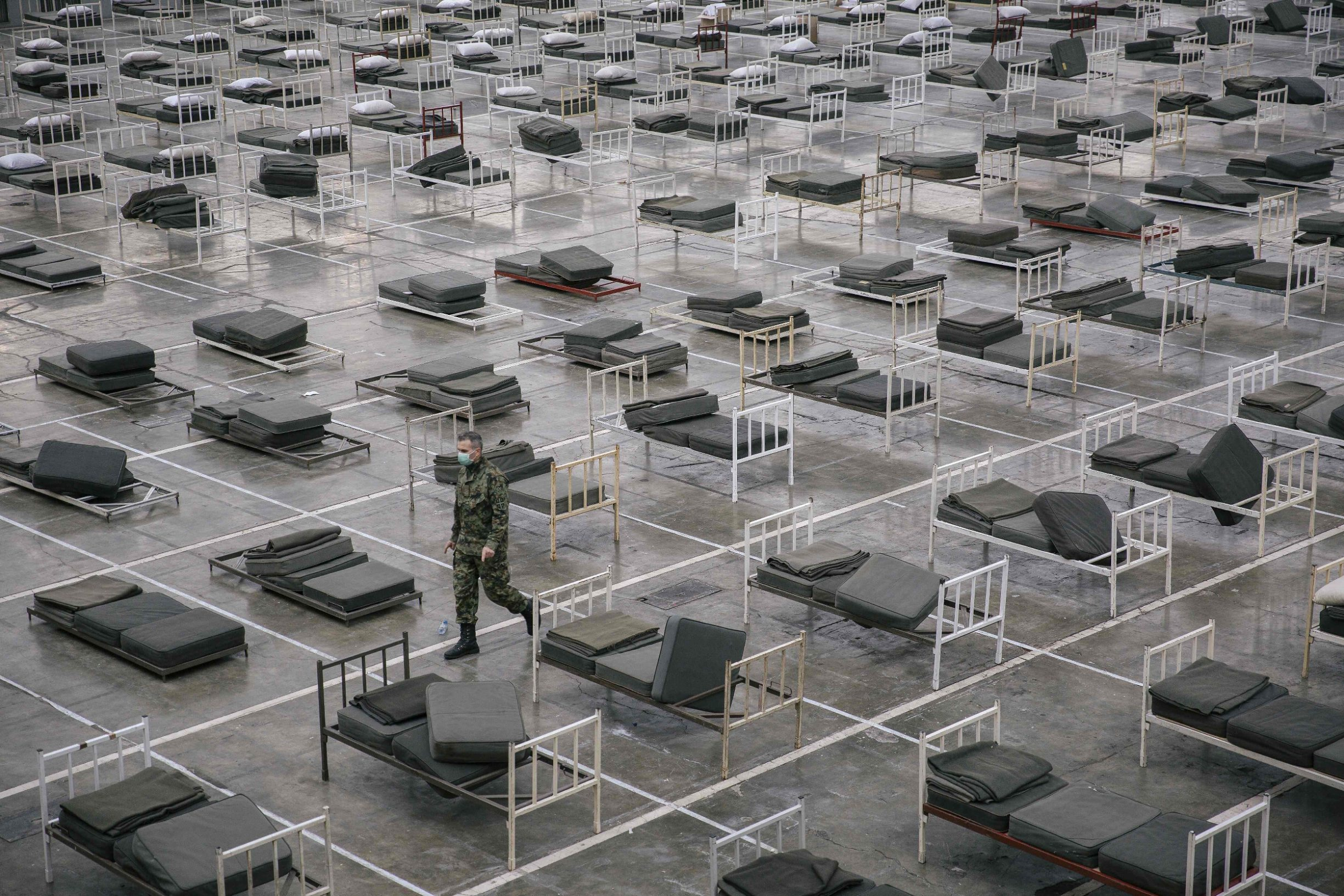 TOPSHOT - A Serbian military personal wearing a protective mask walks amongst beds set up inside a hall at the Belgrade Fair to accommodate people suffering from mild symptoms of the coronavirus disease (COVID-19) on March 24, 2020. - More than 200,000 coronavirus cases have been declared in Europe, according to an AFP tally on March 24, 2020. (Photo by Vladimir Zivojinovic / AFP)